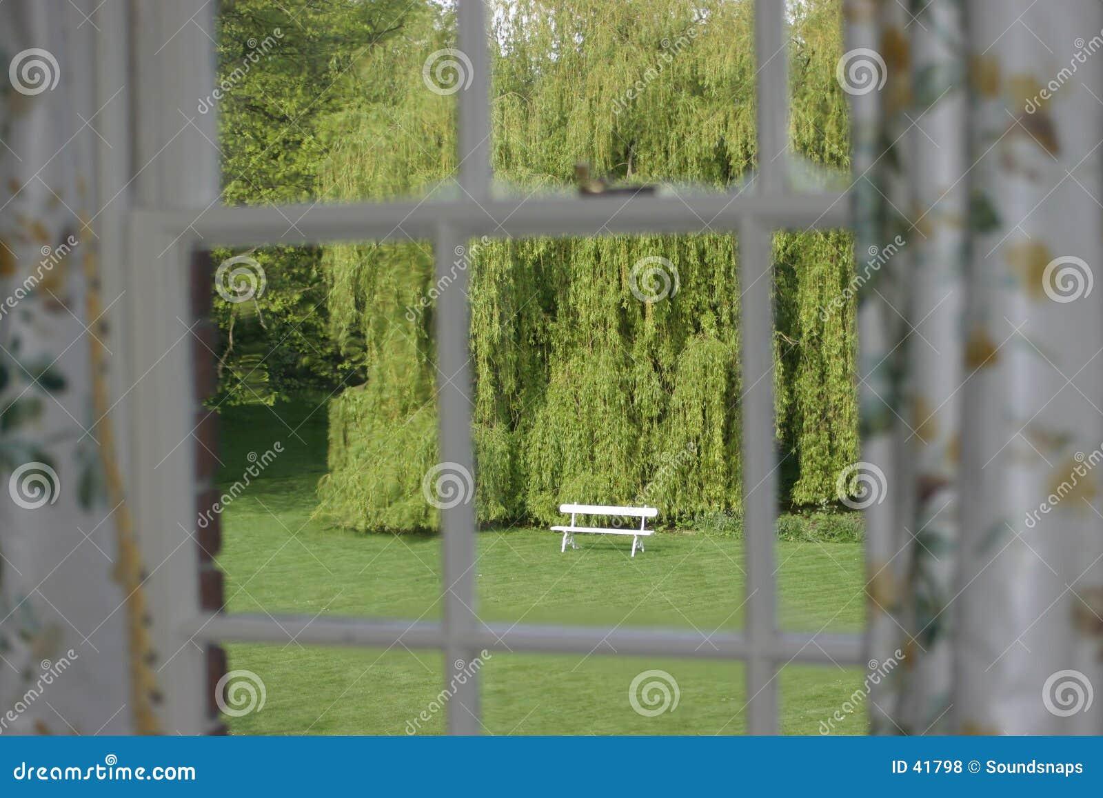 De Zetel van de tuin die door venster wordt gezien