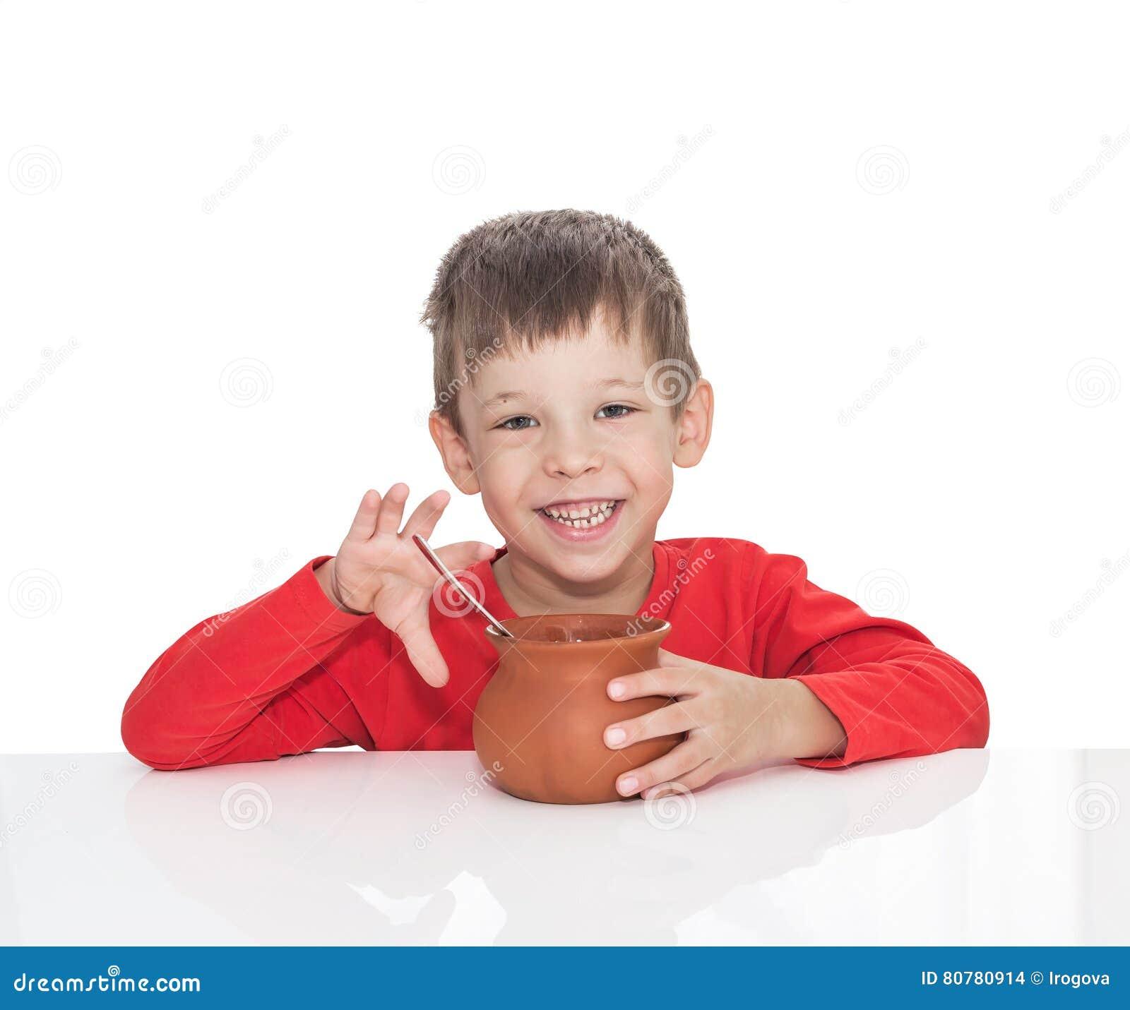 De zieke vijf jaar oude jongen zit bij een witte lijst en eet met een lepel van een kleipot - Jaar oude kamer van de jongen ...