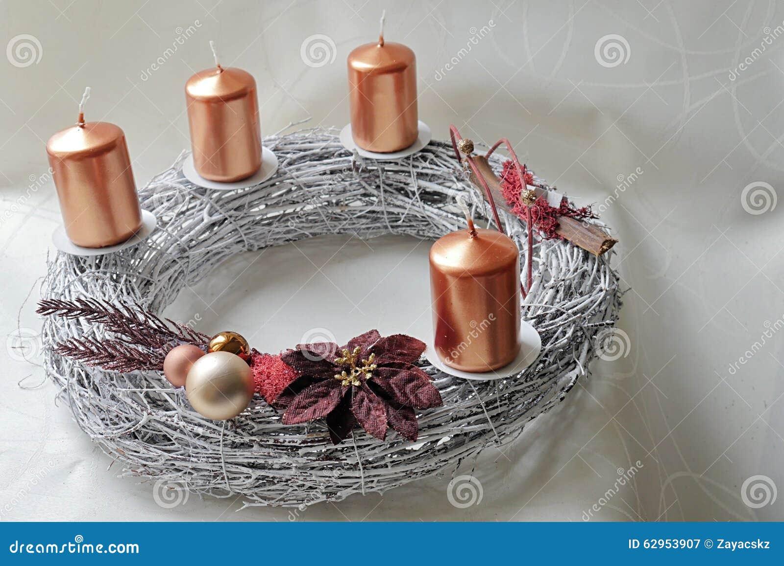 De zilveren kroon van de mandewerkkomst met brons gekleurde kaarsen en christmass decoratie