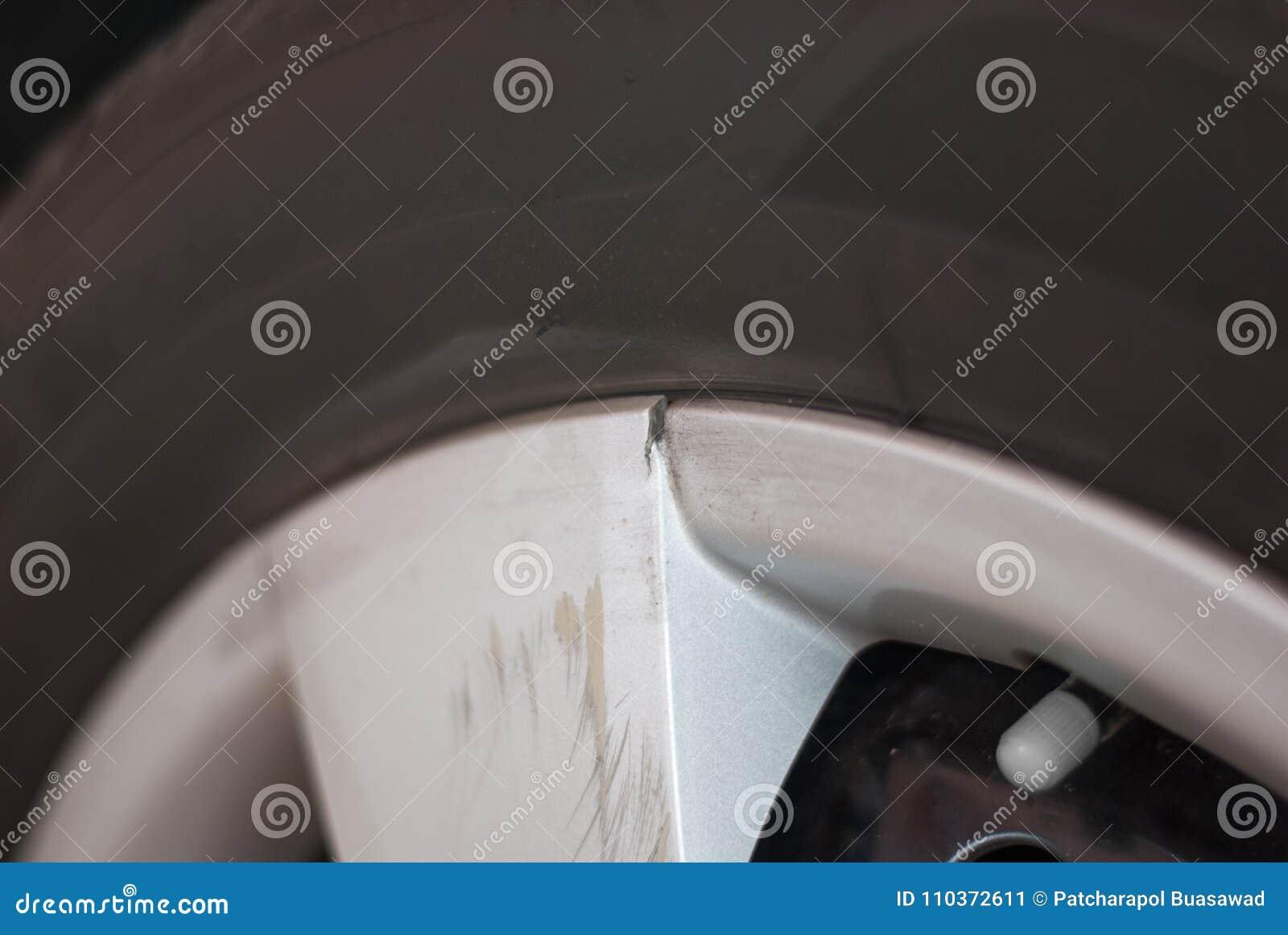 De zilveren rand van de autoband is gebroken en gekrast wegens het raken van s