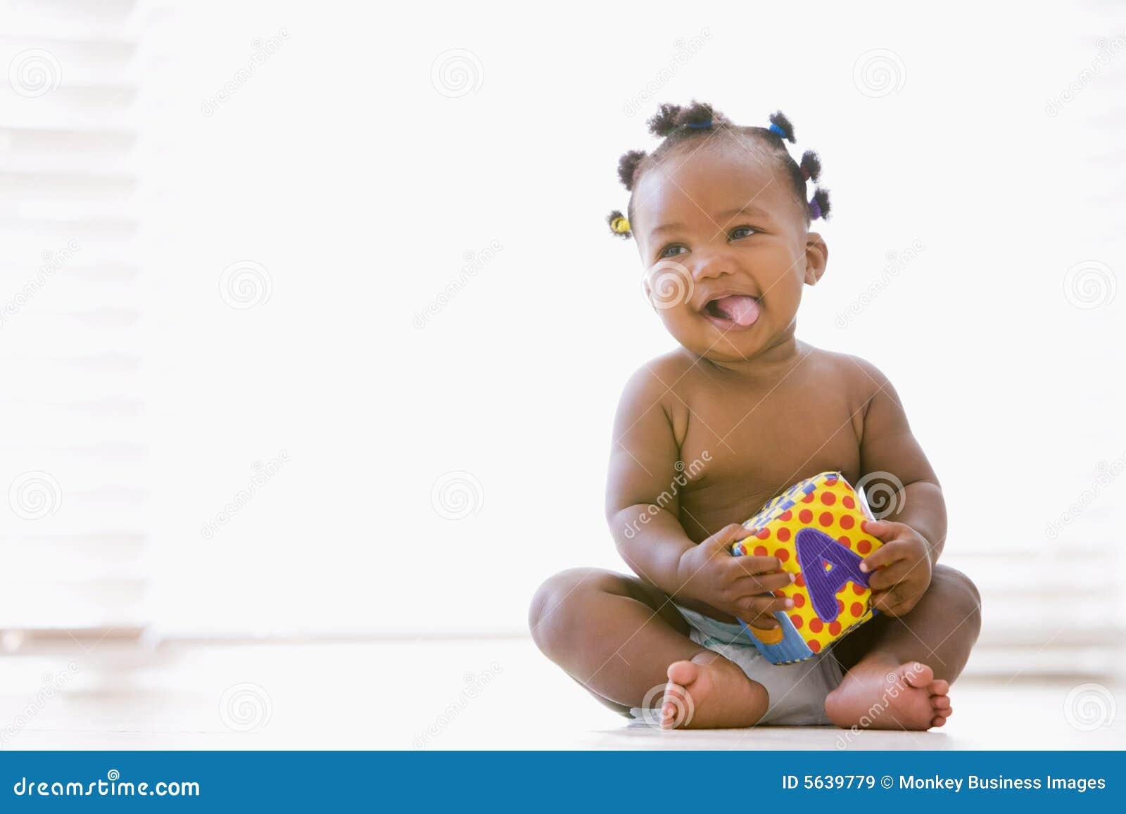 De zitting van de baby binnen met blok het glimlachen