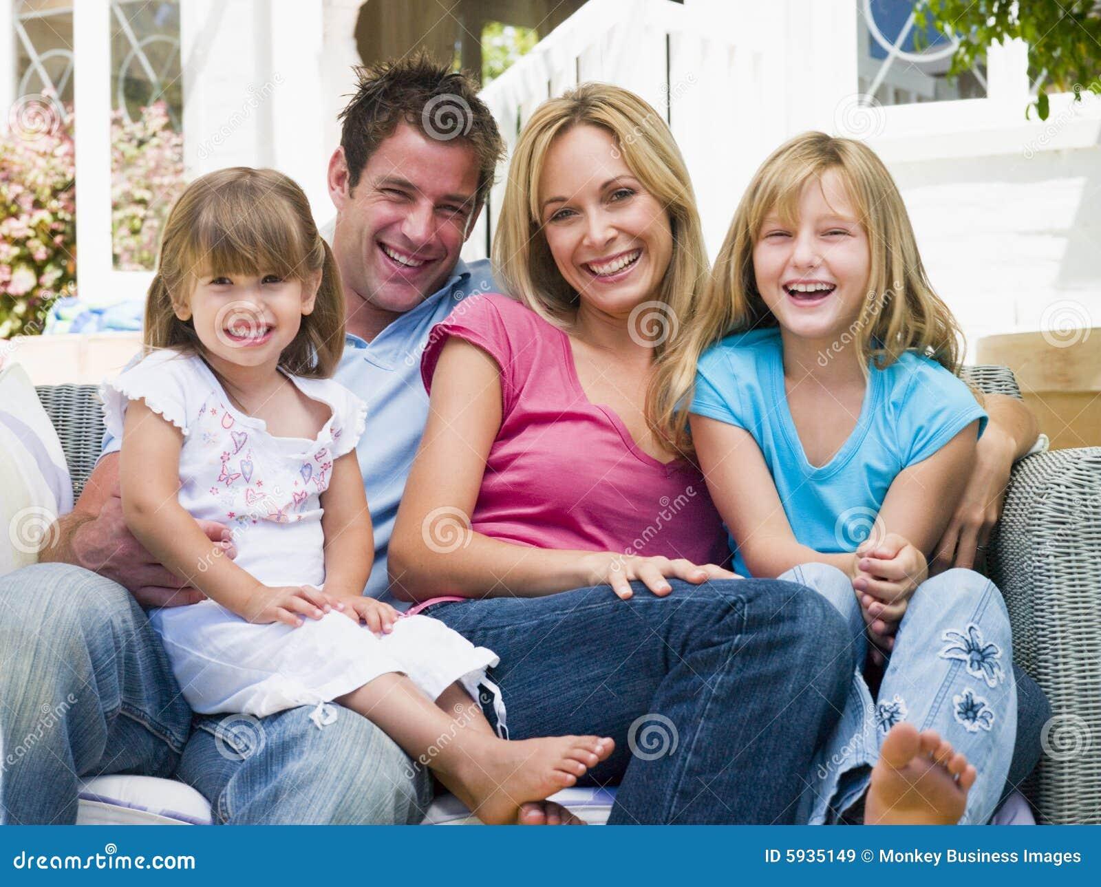 De zitting van de familie bij terras het glimlachen