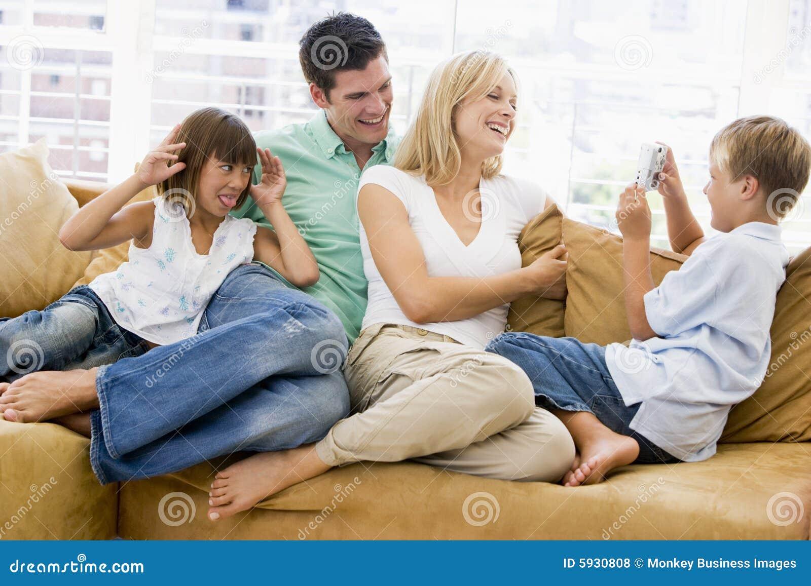 De zitting van de familie in woonkamer met digitale camera