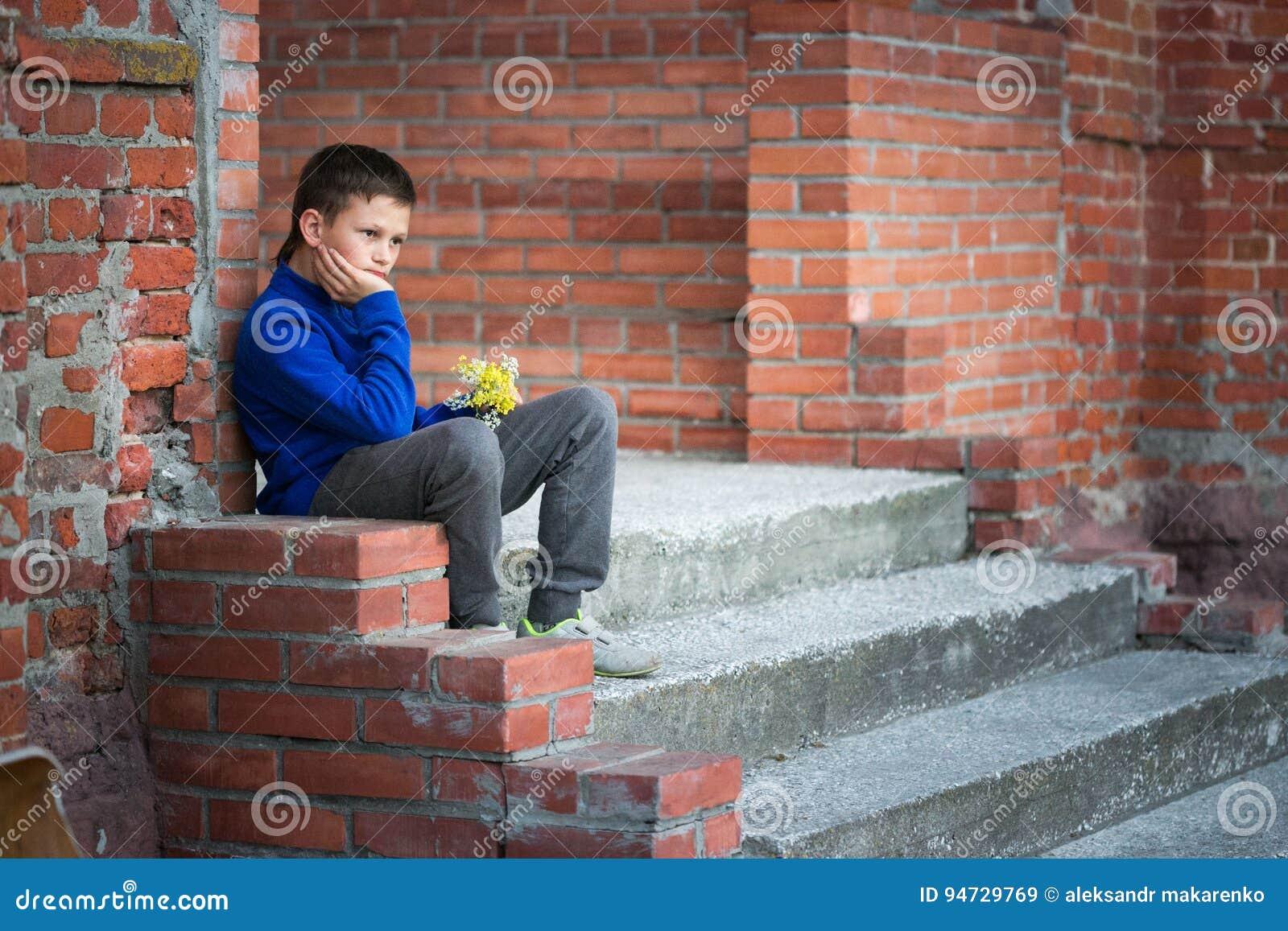 De zitting van de jongenstiener op portiek thuis