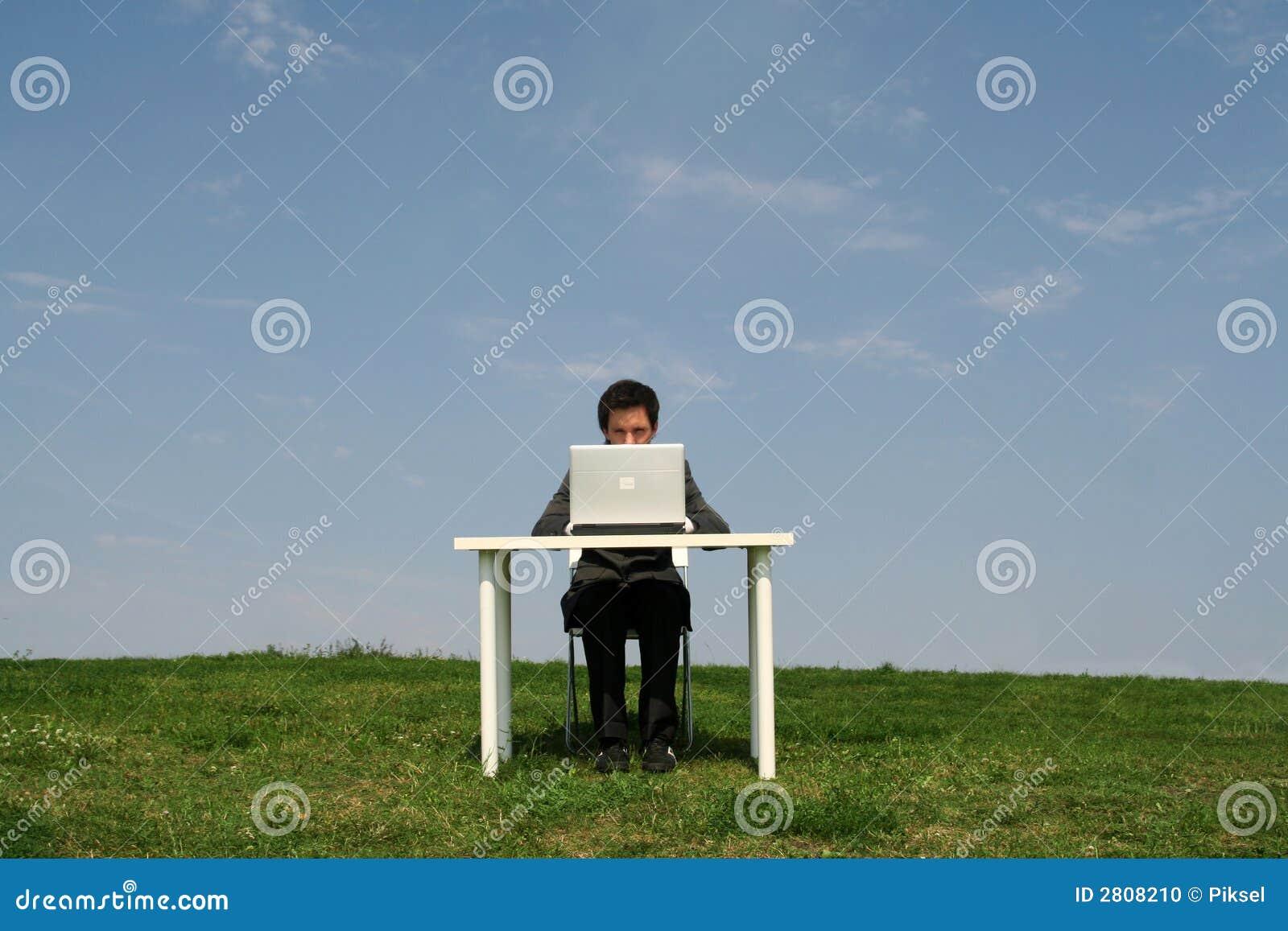 De zitting van de mens bij bureau, in openlucht