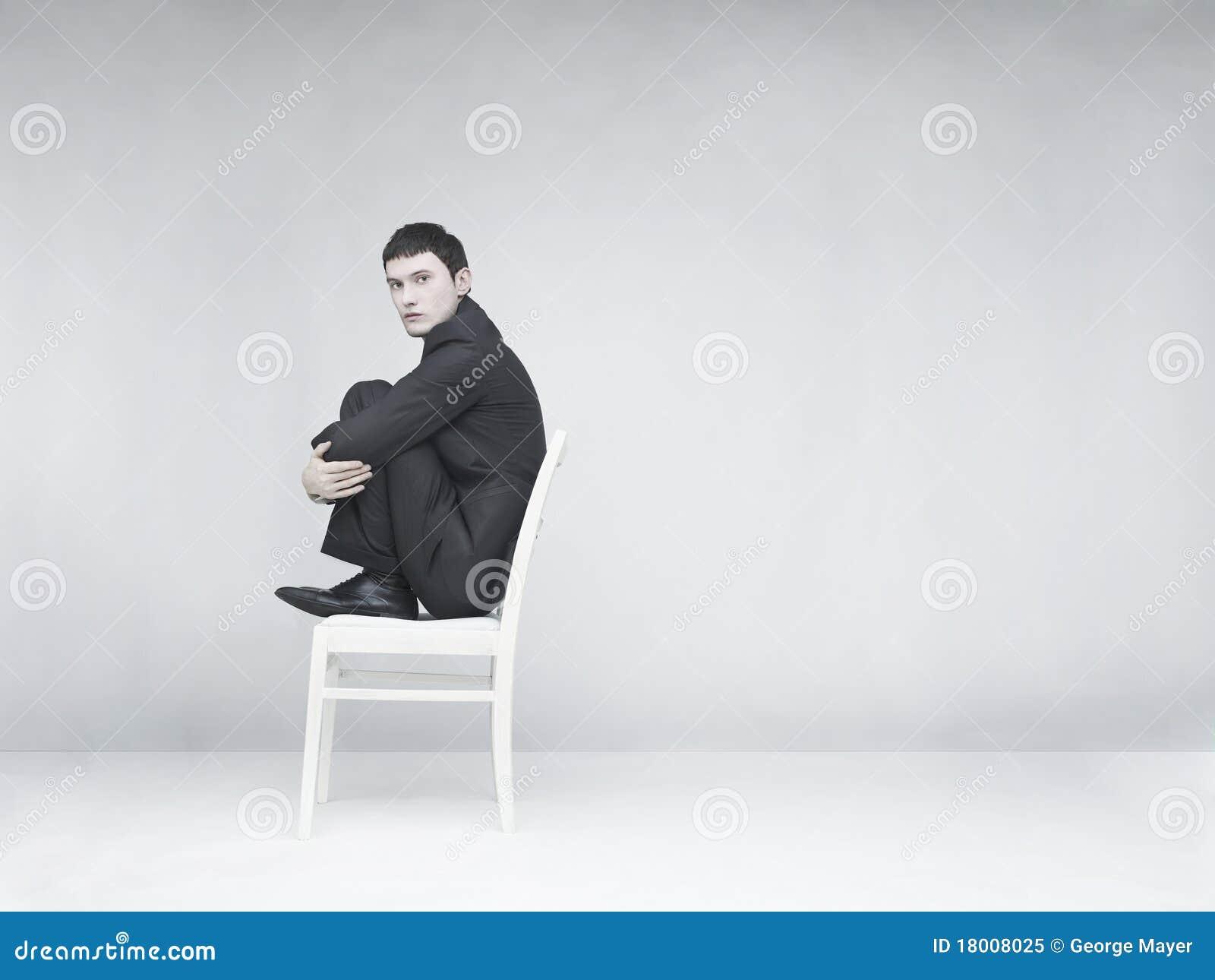 De zitting van de mens op een witte kruk