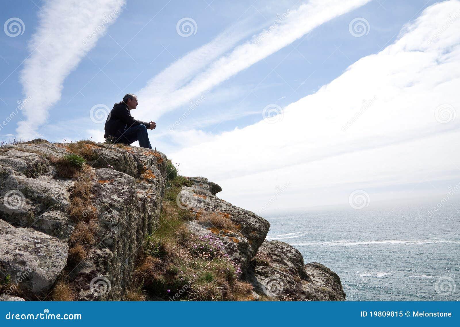 De zitting van de mens op klippenbovenkant