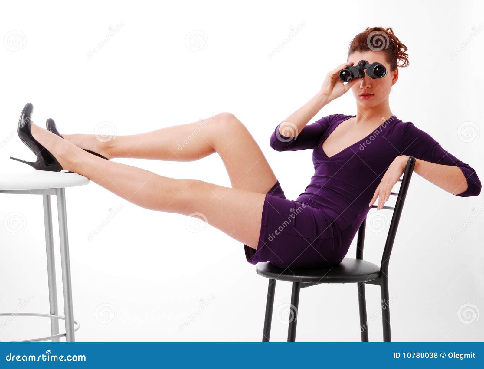 De zitting van de vrouw en het kijken op verrekijkers.