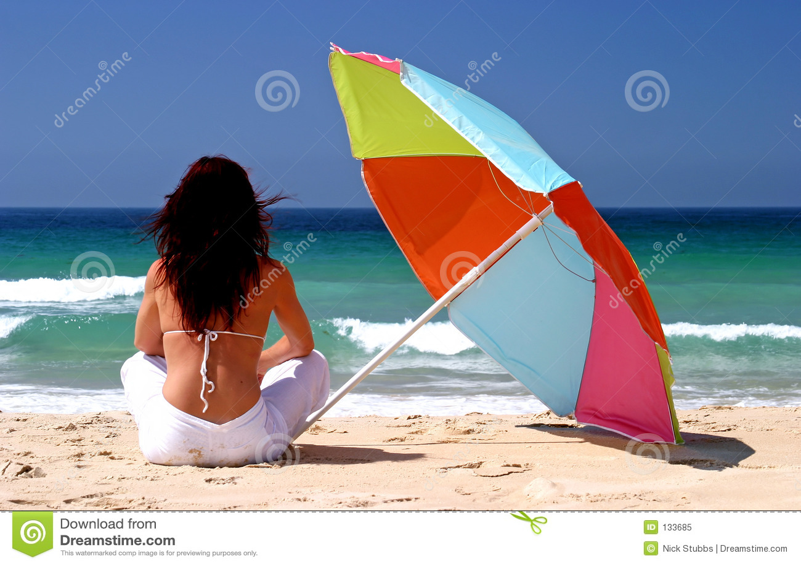 De zitting van de vrouw onder kleurrijke parasol op wit zandig strand