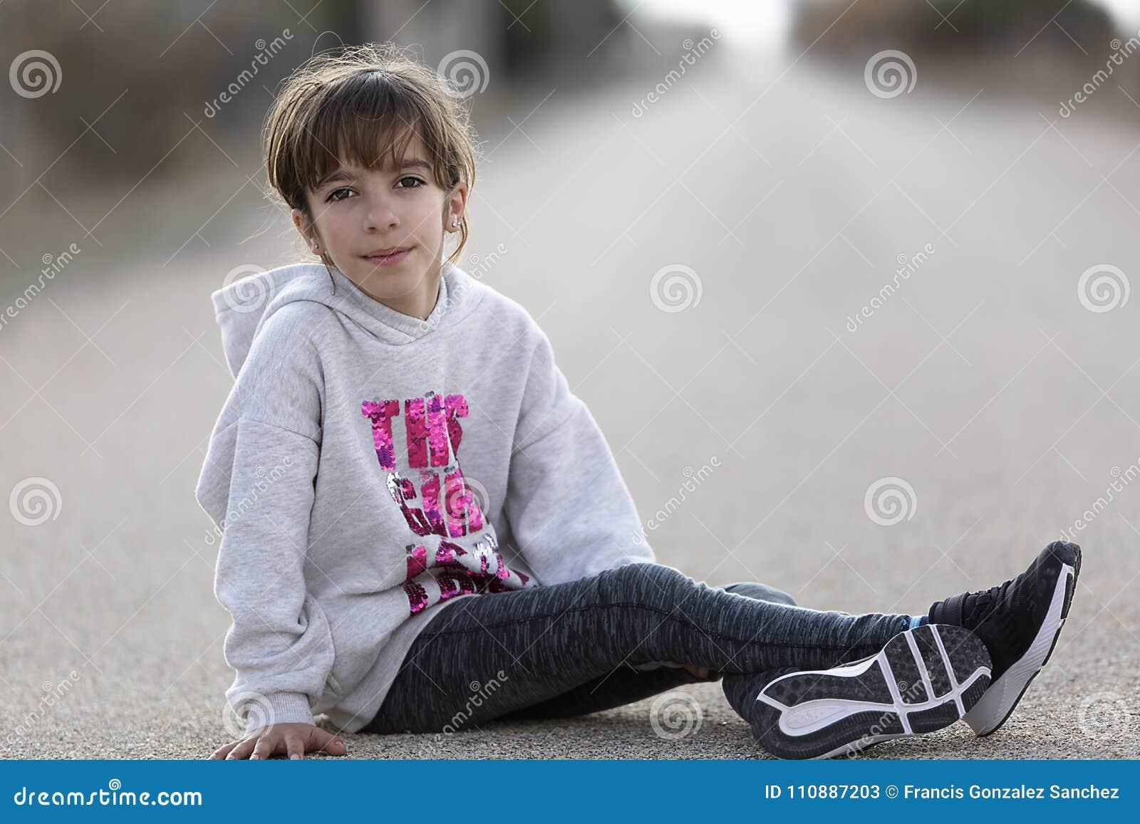 De zitting van het 10 éénjarigenmeisje op de vloer van een auto die ca bekijken