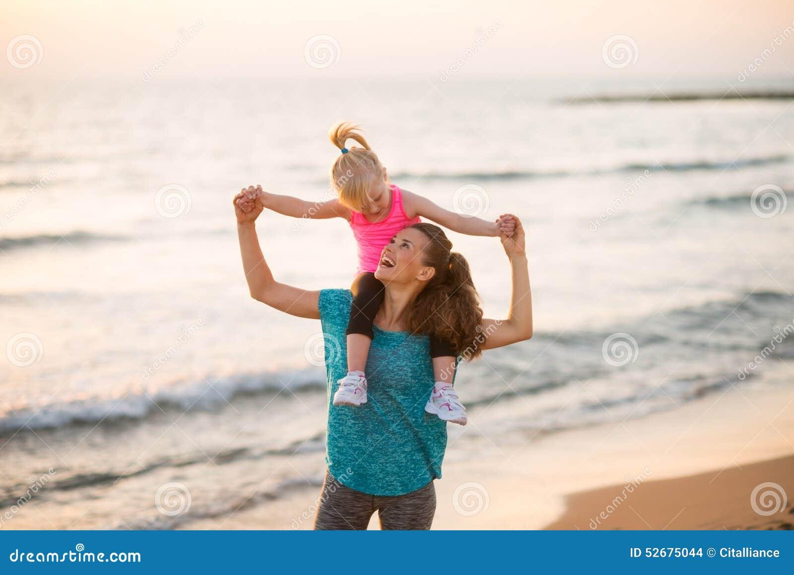 De zitting van het babymeisje op schouders van moeder op strand