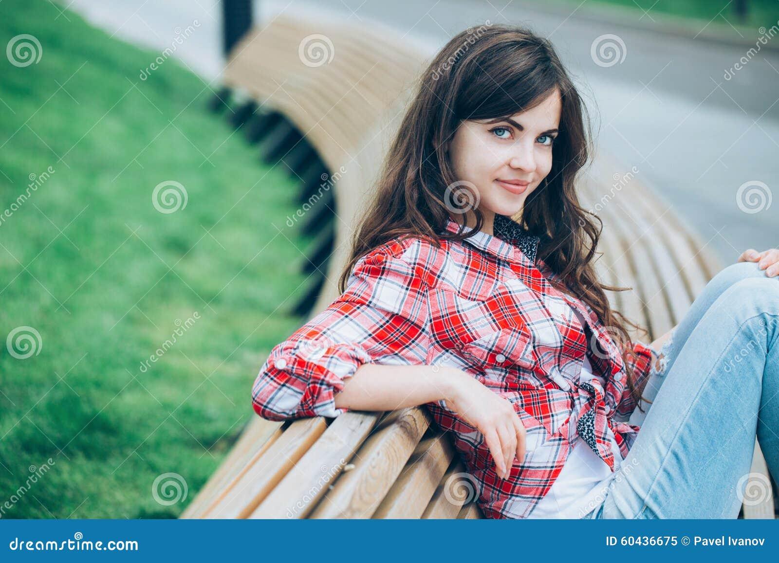 De zitting van het meisje op een bank