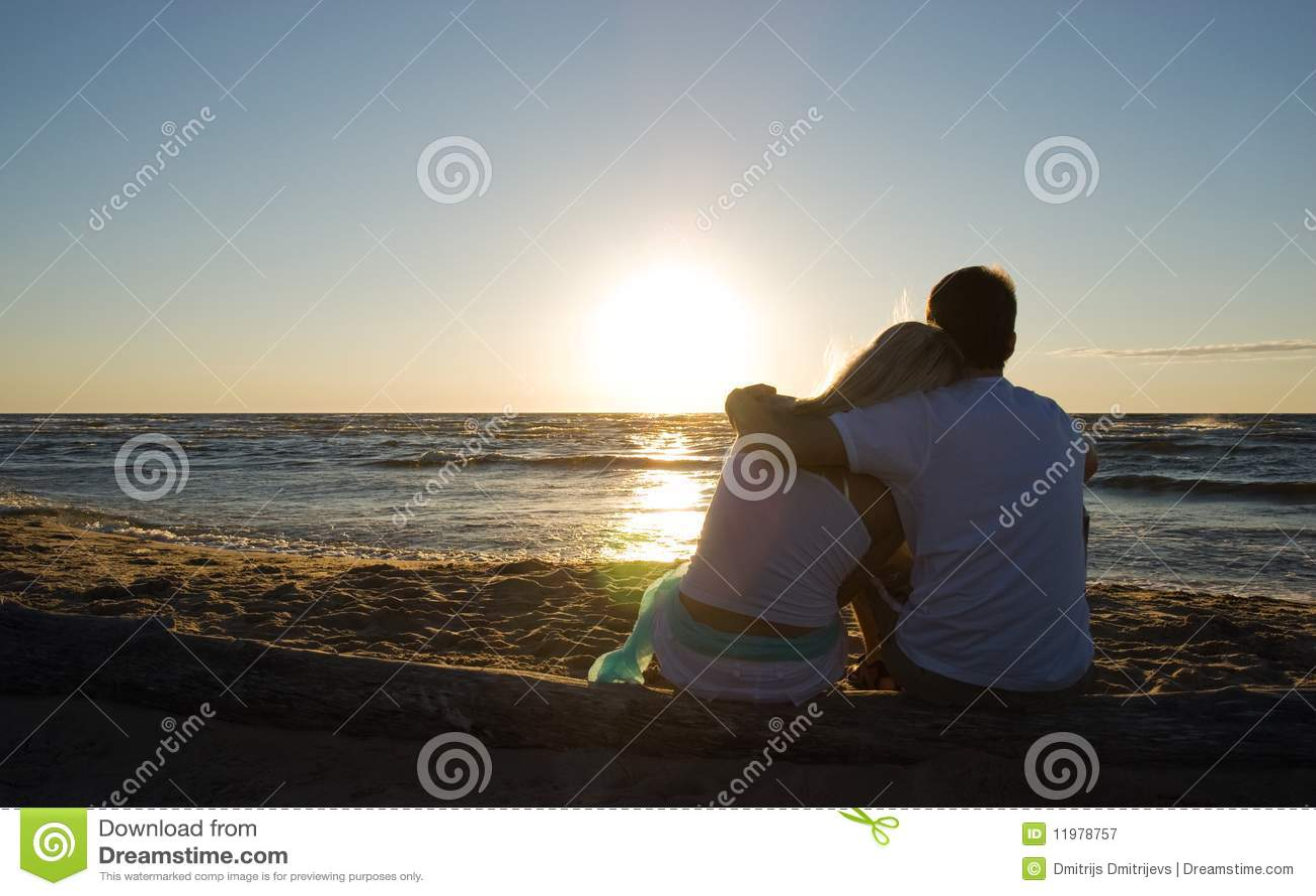 De zitting van het paar dichtbij het overzees op zonsondergang