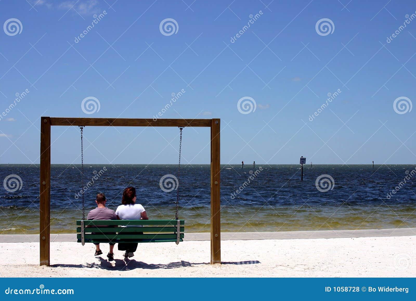 De zitting van het paar op een schommeling bij het strand in Florida