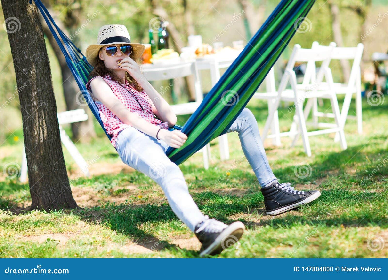 De zitting van het tienermeisje in hangmat op tuin partij en het eten van cake
