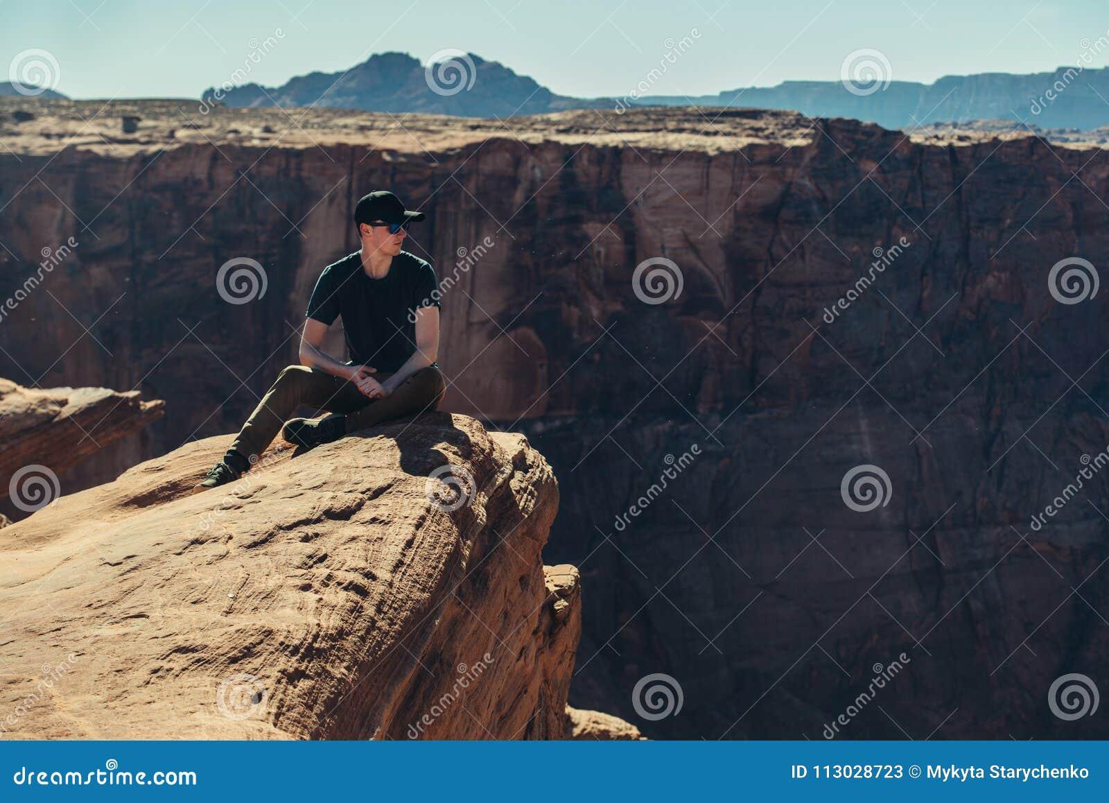 De zitting van de toeristenmens op de de randrots van de bergklip en geniet van de mening na wandeling bij hete de zomerdag in Gr