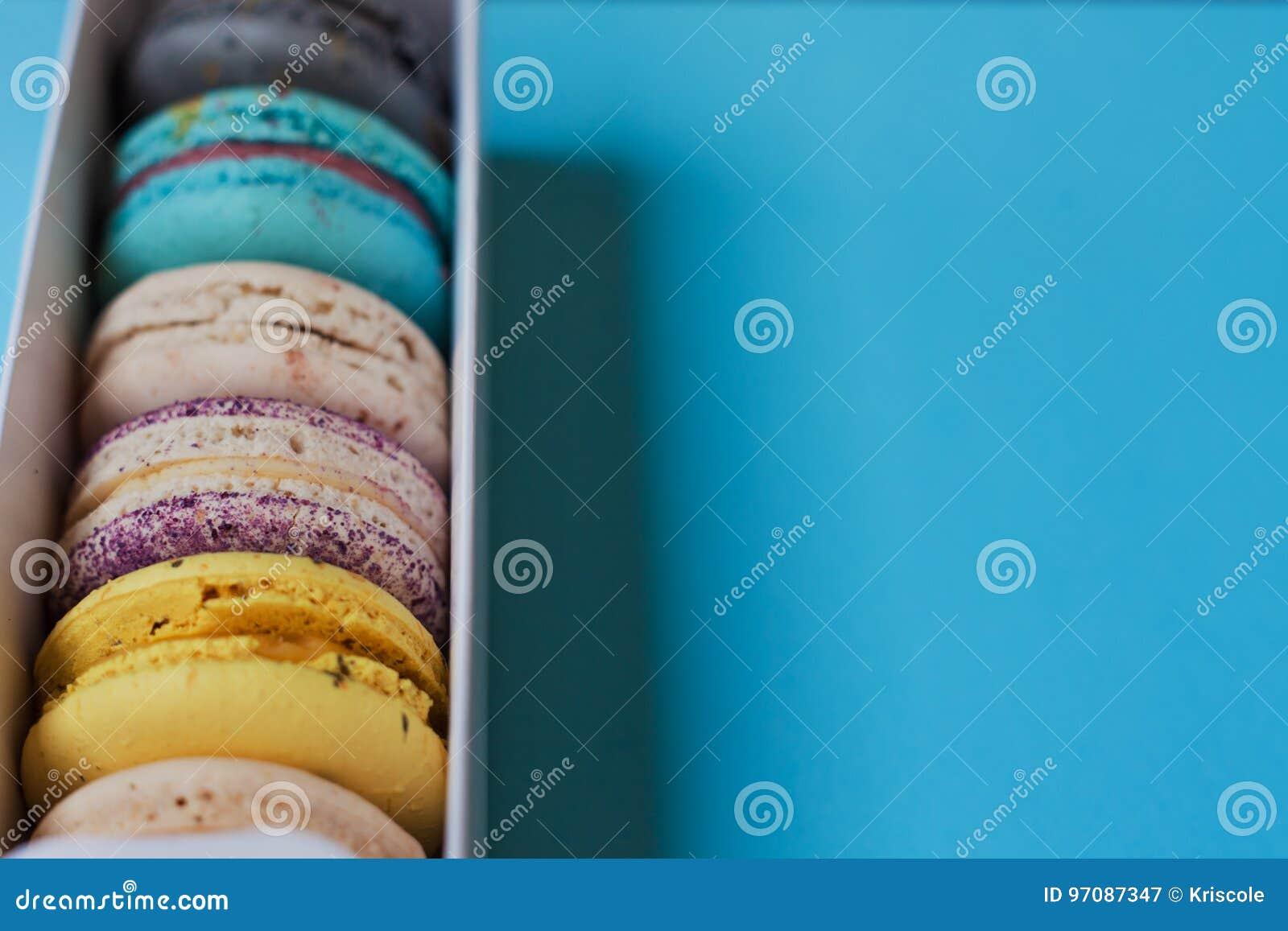 De zoete macaroni van de giftdoos op een blauwe achtergrond Vrije ruimte op het recht