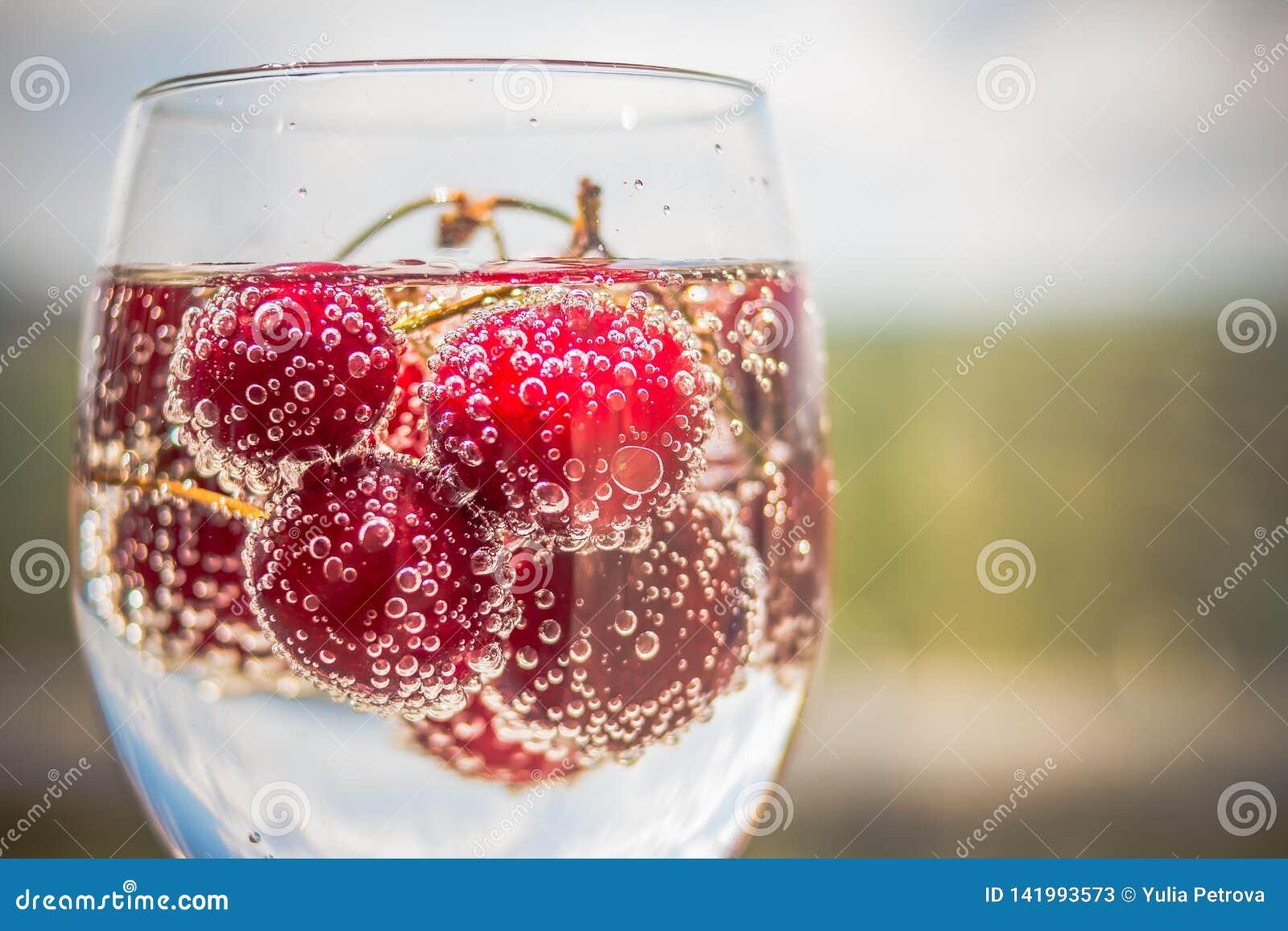 De zomer bevroor verfrissingdrank, de limonade van de kersenkola of mojitococktail in lang glas, op lichtblauwe en grijze achterg