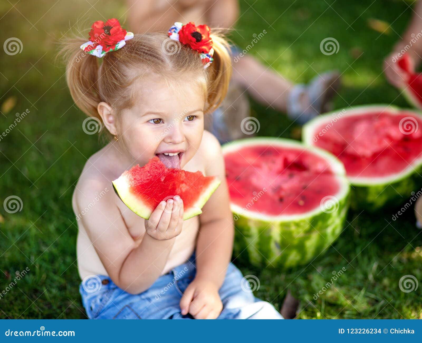 De zomer gezond voedsel De zomer gezond voedsel gelukkig glimlachend kind twee die watermeloen in park eten Close-upportret van l