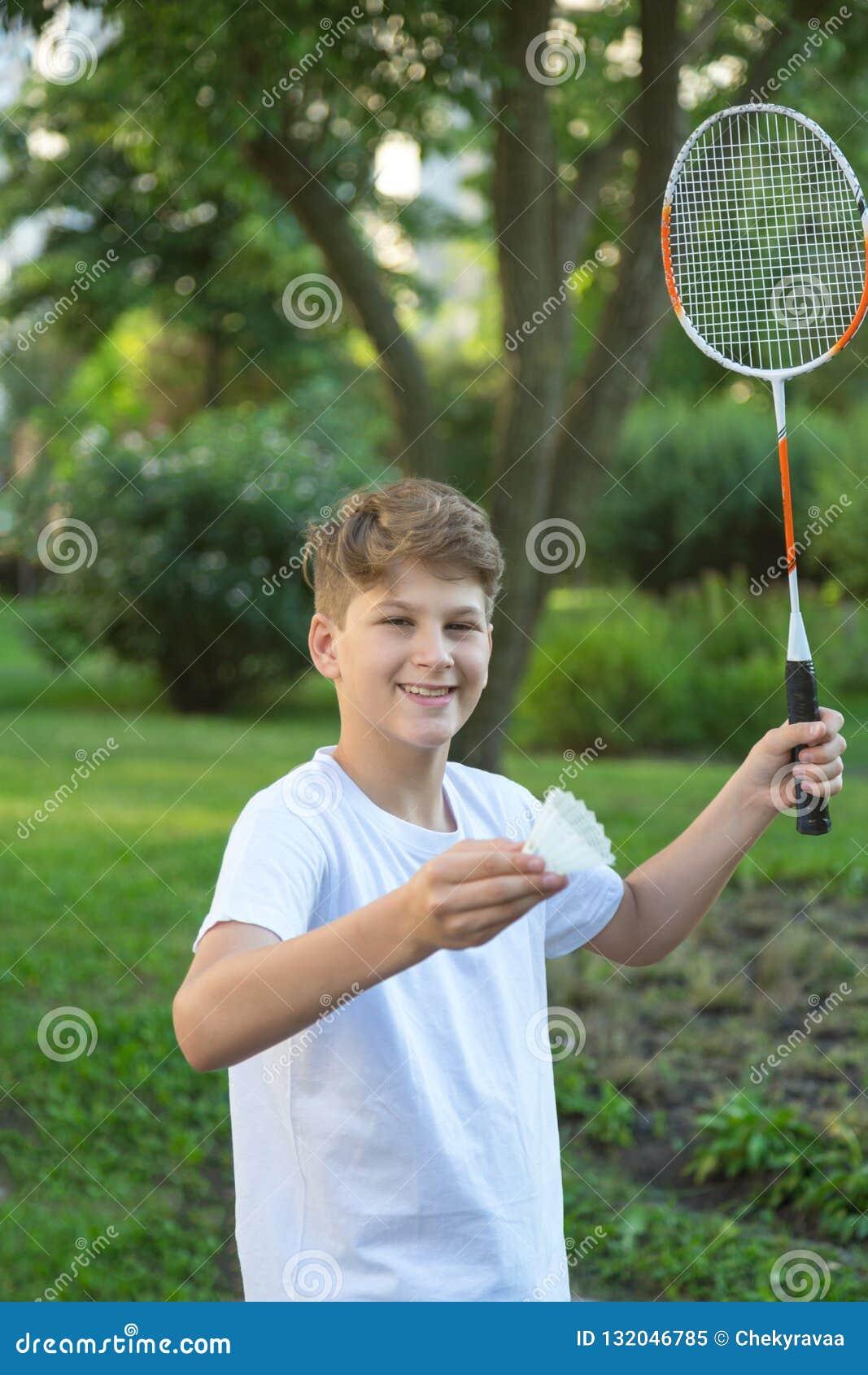 De zomer grappig portret van het leuke speelbadminton van het jongensjonge geitje in groen park Sport, gezonde levensstijl