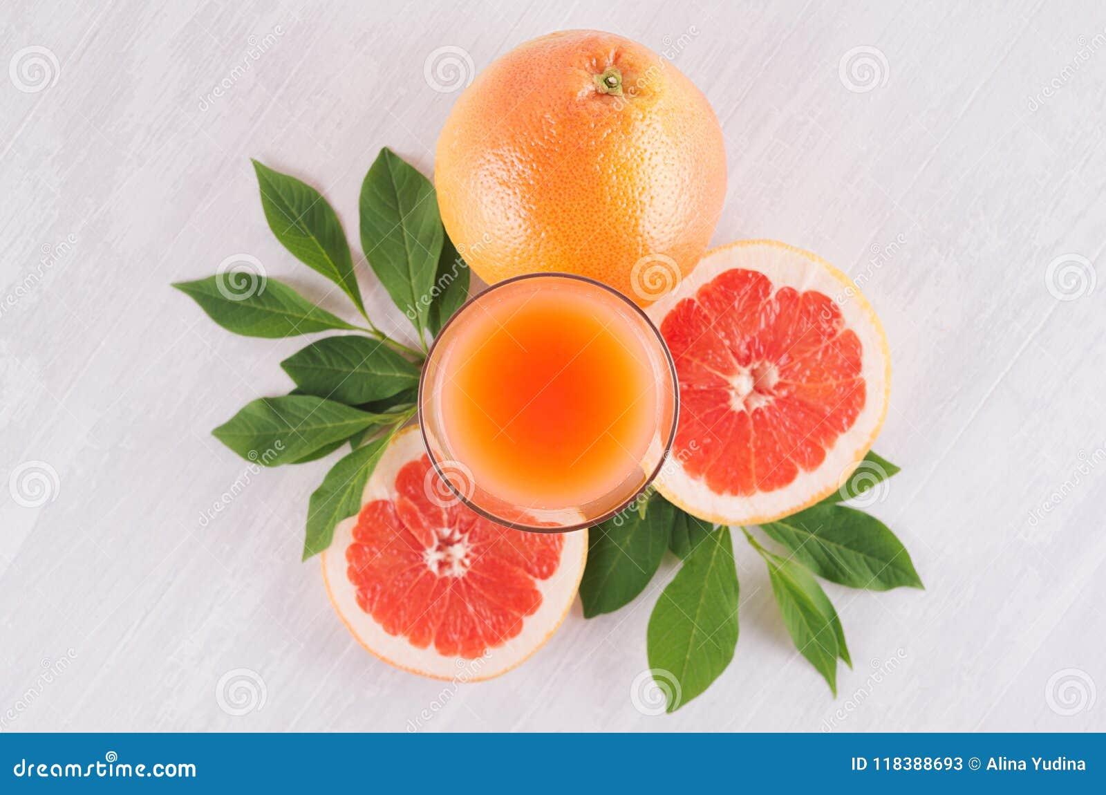 De zomer heldere verse roze cocktail van grapefruits met groene bladeren, plakgrapefruit op witte houten achtergrond, hoogste men