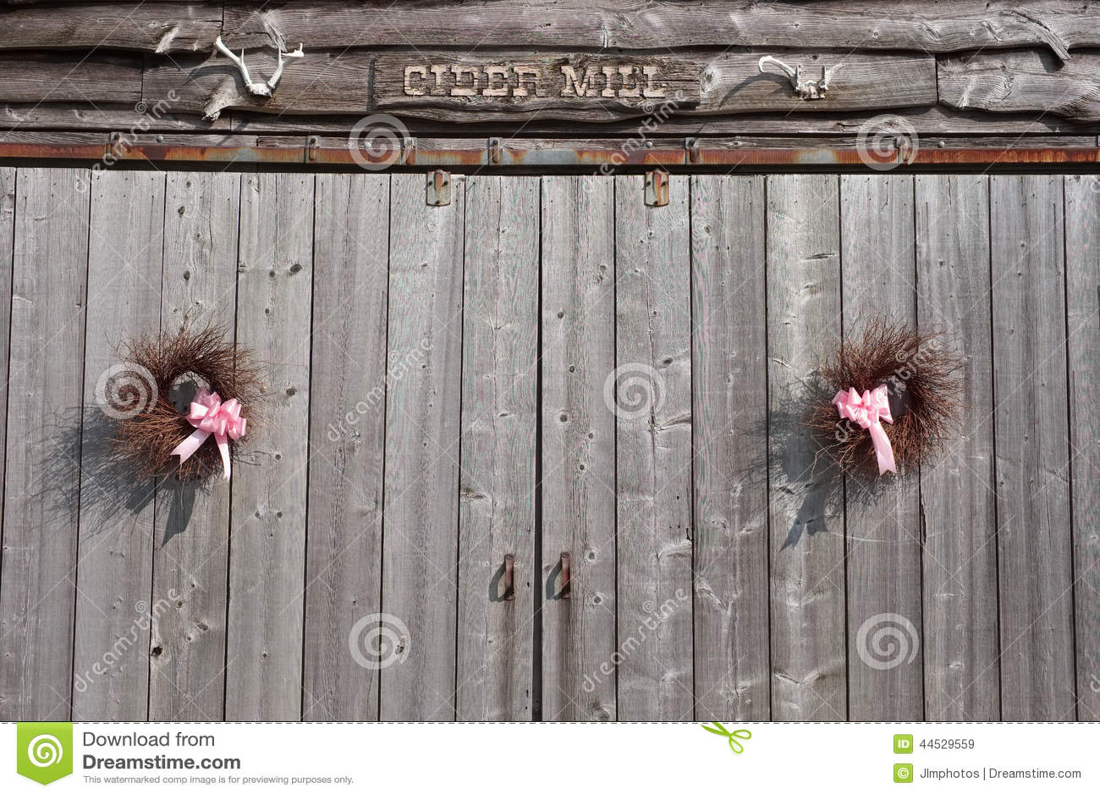 De zomer met de hand gemaakte kronen die op oude staldeuren hangen
