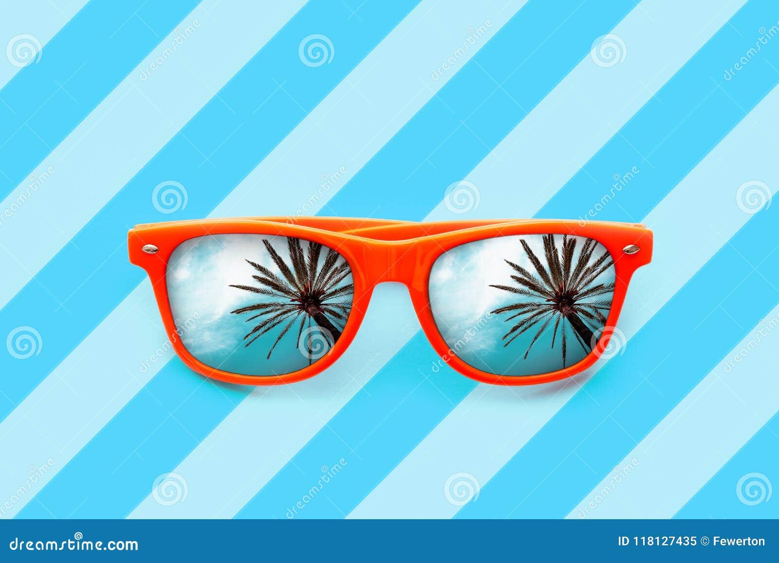 De zomer oranje die zonnebril met palmenbezinningen op blauwe achtergrond met diagonale strepen worden geïsoleerd