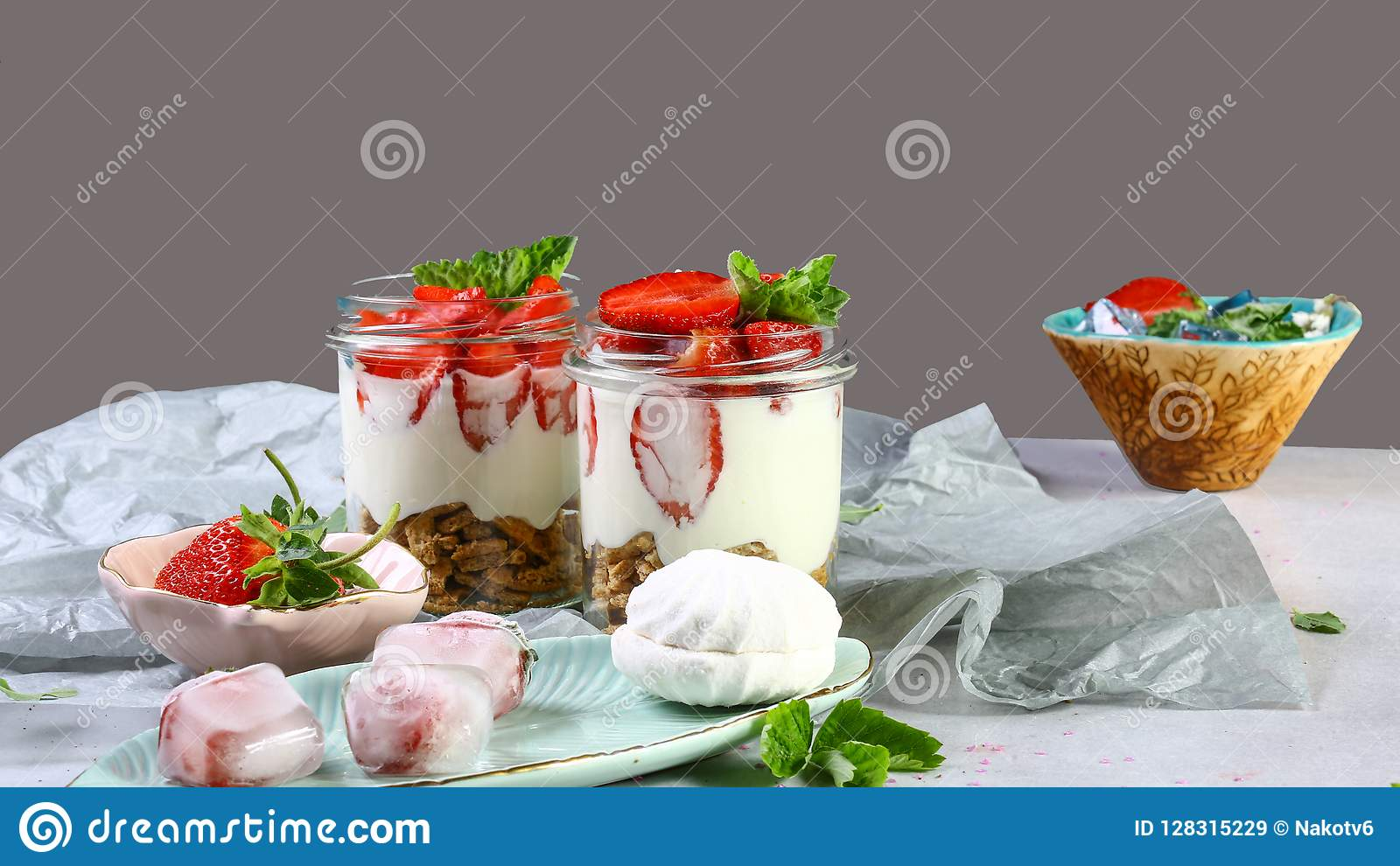 De zomerdessert, klassieke die kaastaart met aardbeien met muntbladeren worden verfraaid Voor een grijze steen of een concrete li