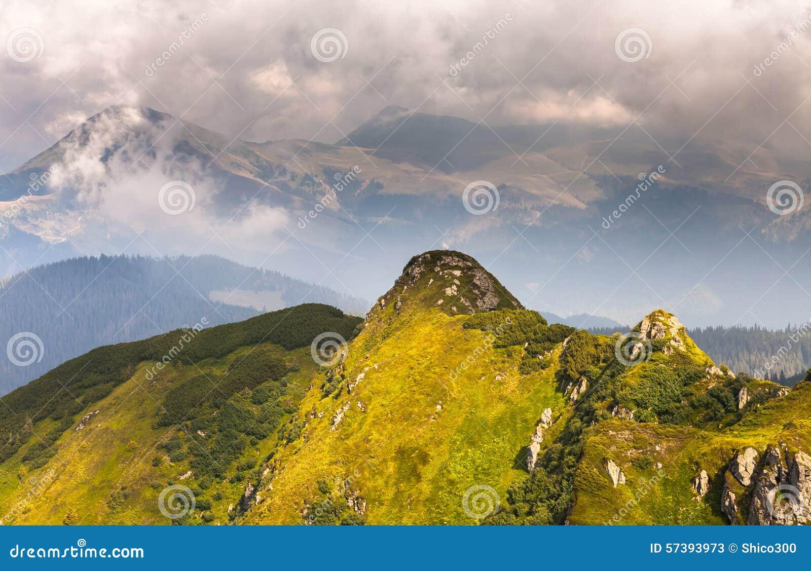 De zomerlandschap in bergen en de donkerblauwe hemel met wolken