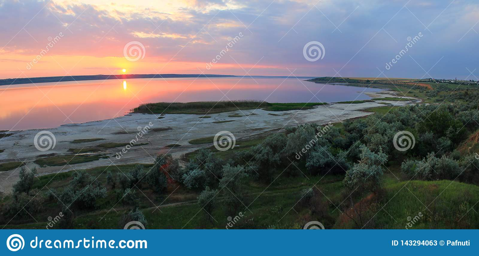 De zomerlandschap op de banken van het meer bij zonsondergang