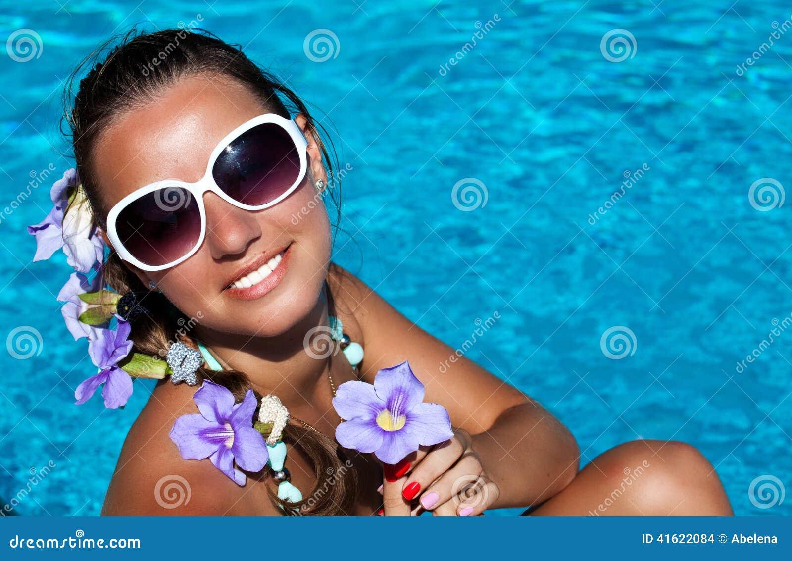 De zomermeisje vrolijk in zonnebril die over de bedelaars van de wateraard genieten van
