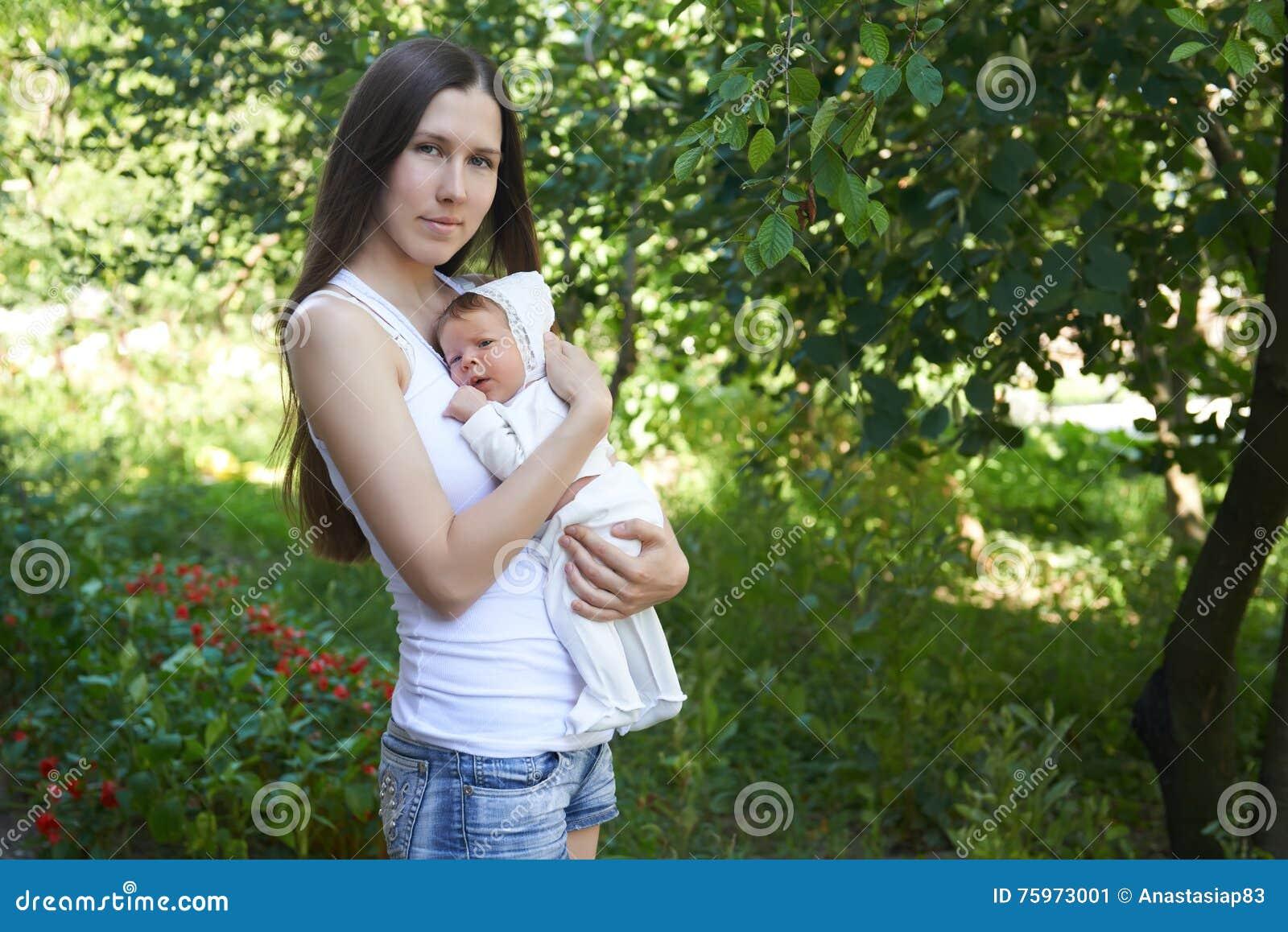 De zomerportret van een jonge moeder met een pasgeboren kind