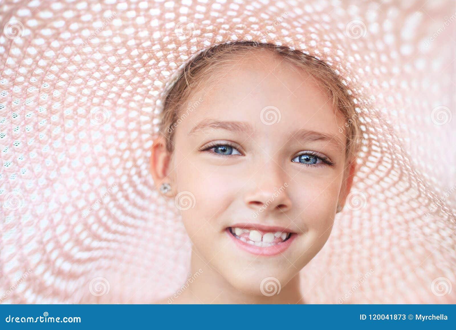 De zomerportret van een mooi meisje in een roze hoed