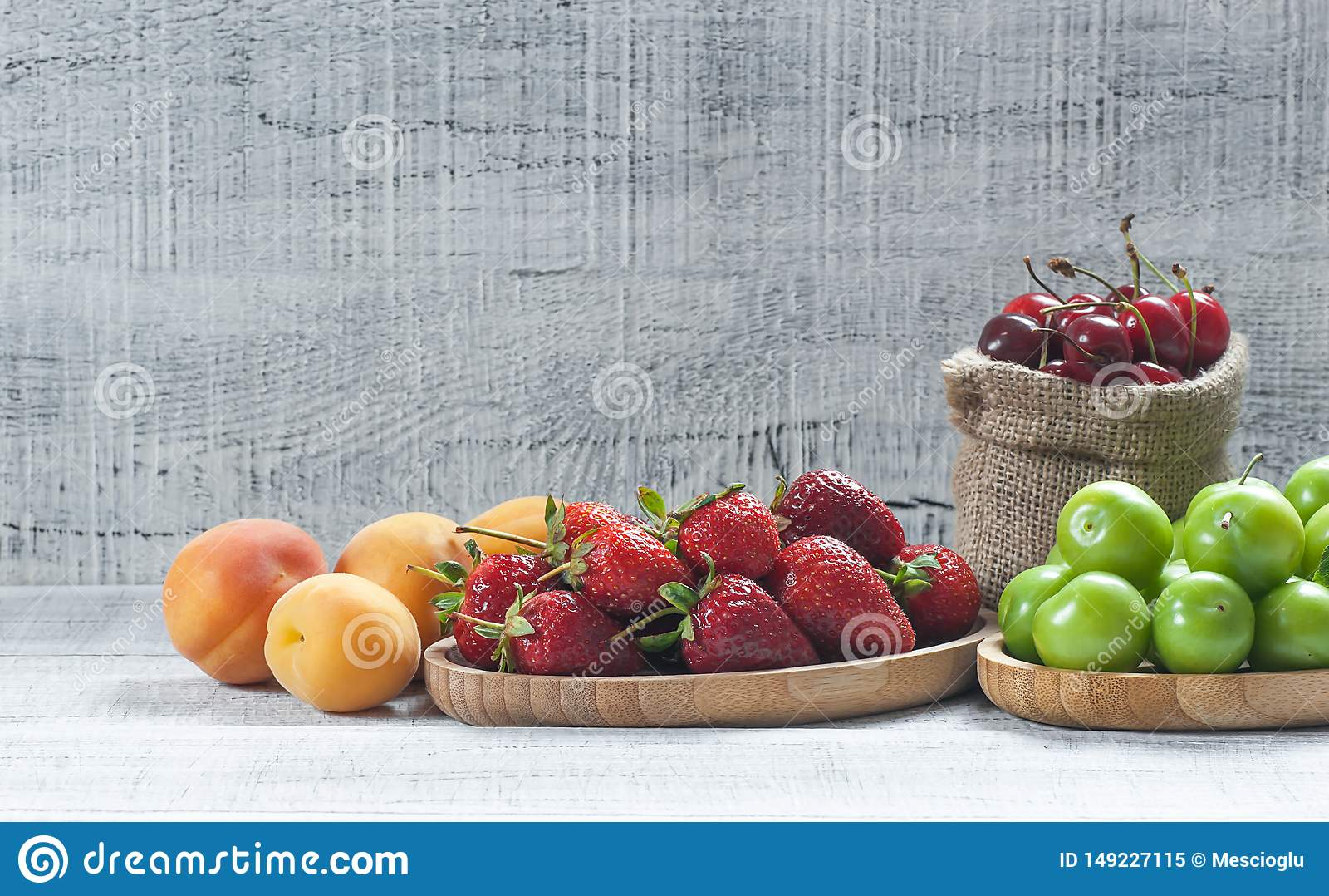 De zomervruchten, groene pruim, rode kers, aardbei, abrikoos op witte houten achtergrond
