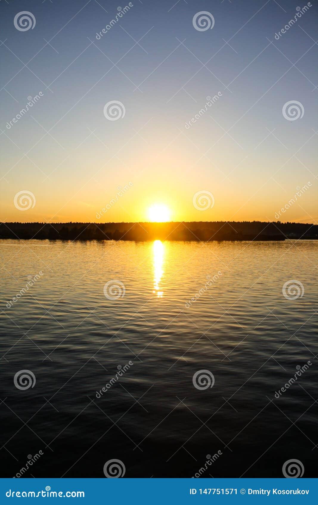 De zomerzonsondergang over de rivier