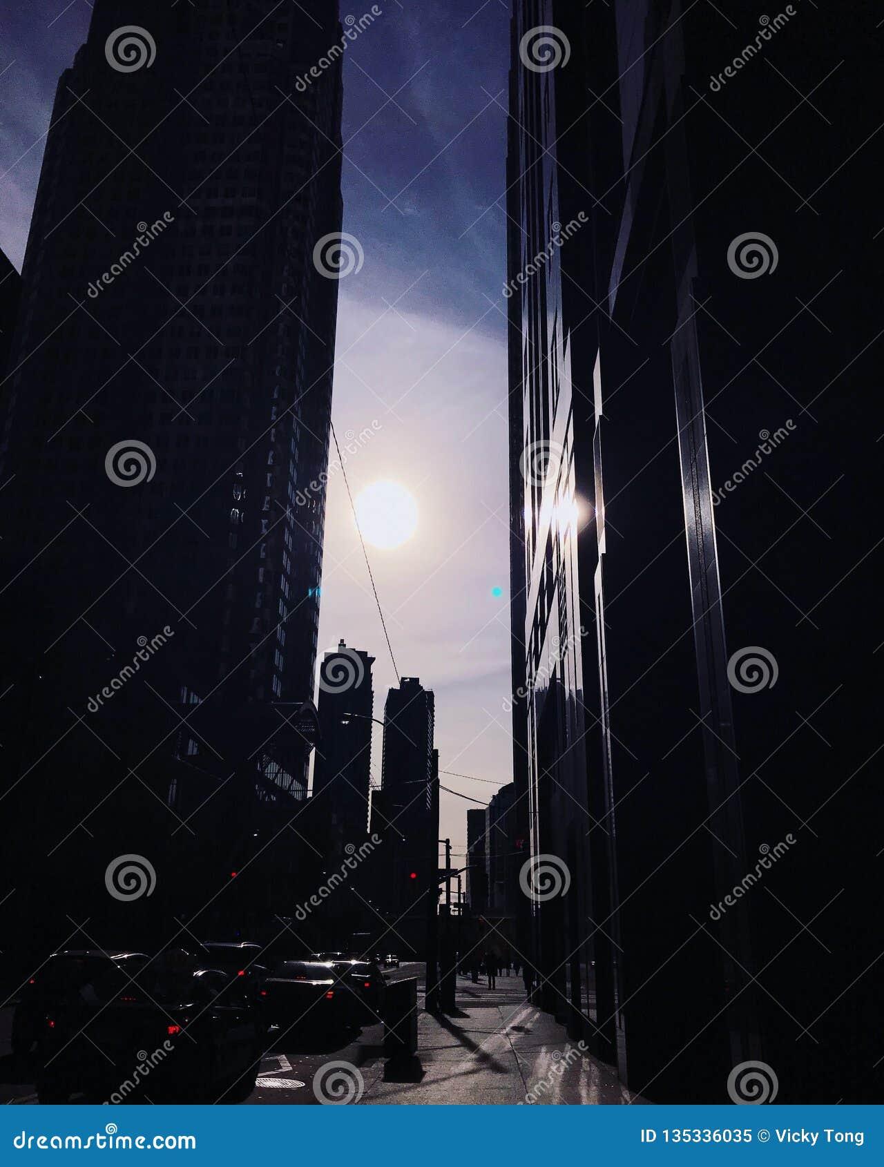 De zon daalt tussen gebouwen