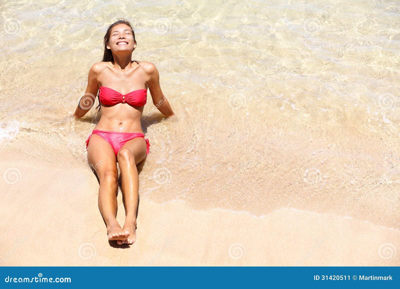 De zon van het de bikinimeisje van de strandvakantie gelukkig looien