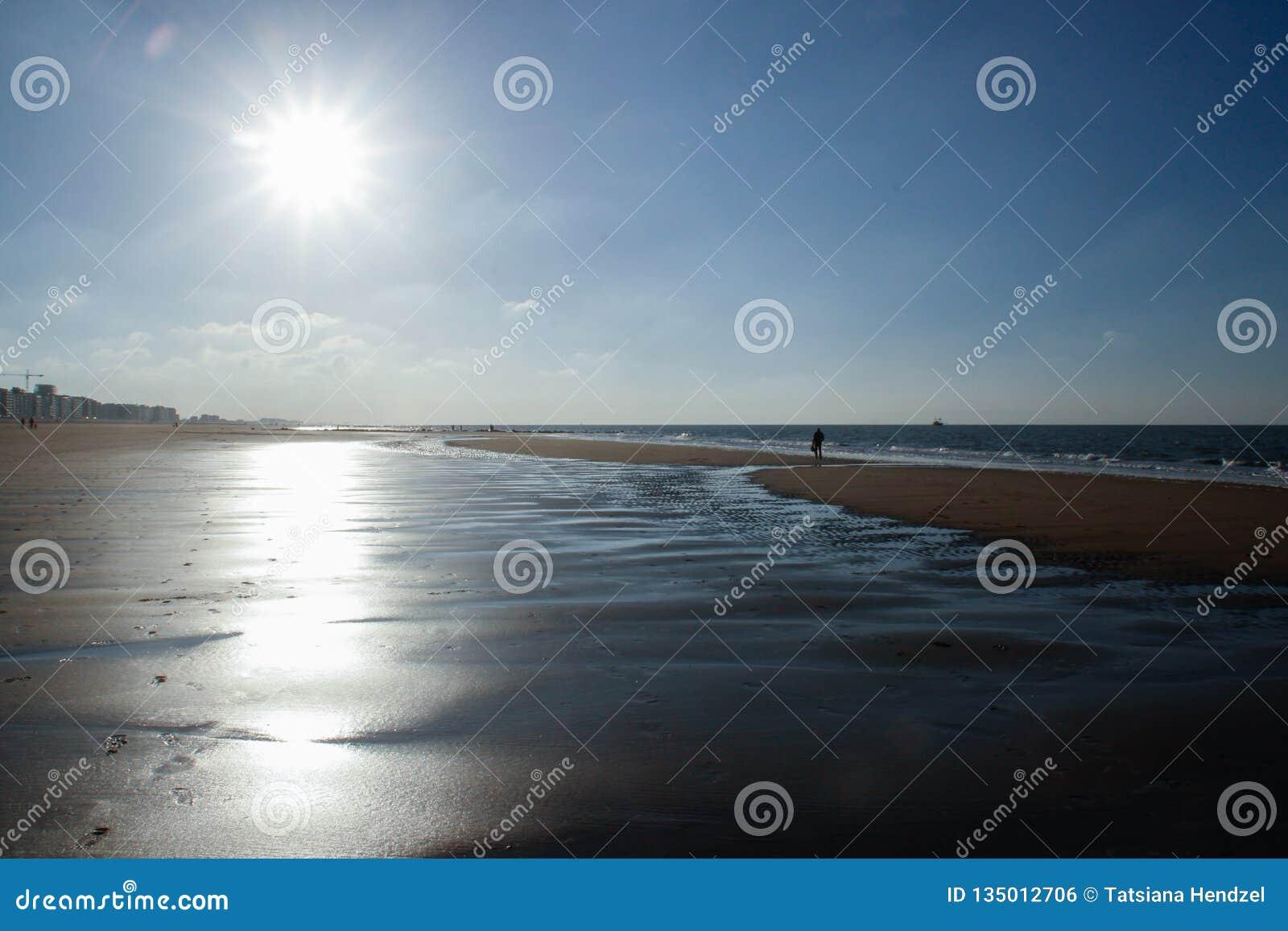 De zon verlicht het verlaten strand van de koude Noordzee in België