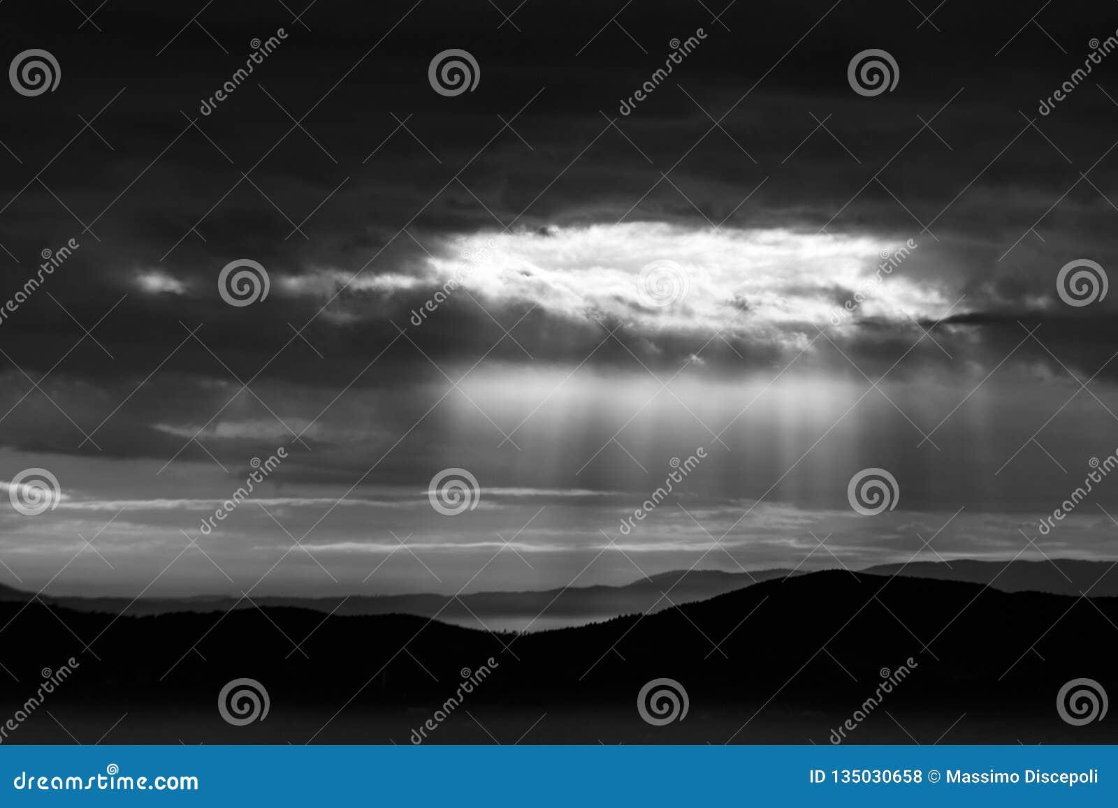 De zonnestraal glanst door wolken over de bergen en een overzees van mist