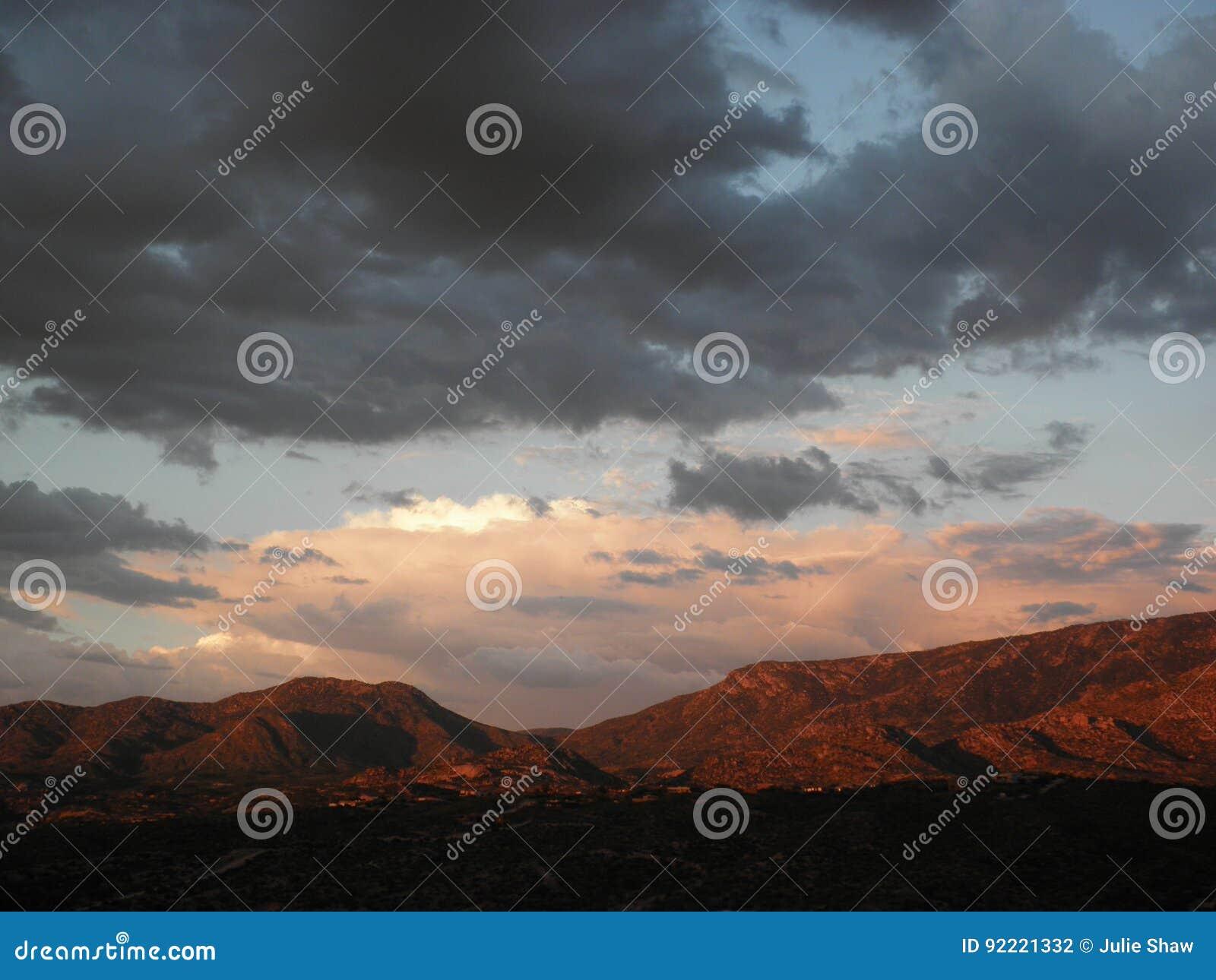 De zonsondergang van moessonwolken over de Pusch-Randbergen in het landschap van Tucson Arizona