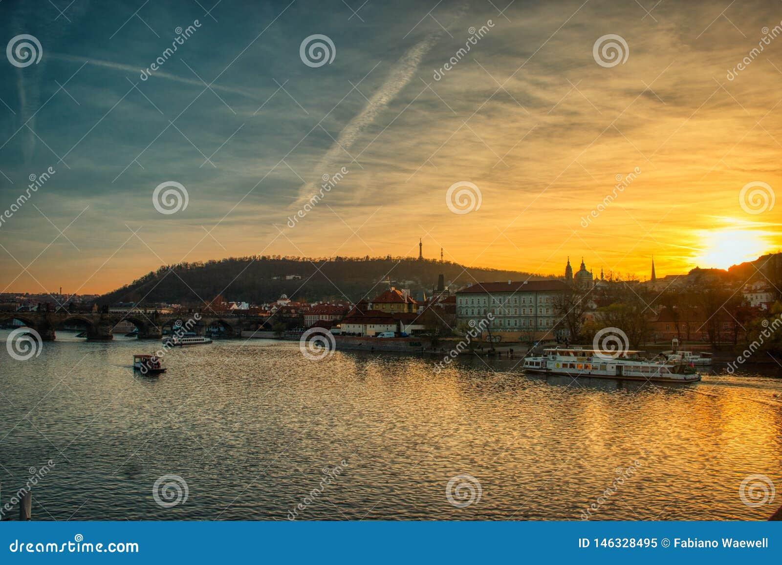 De zonsondergang van Praag door Vltava rivier met boten warm licht