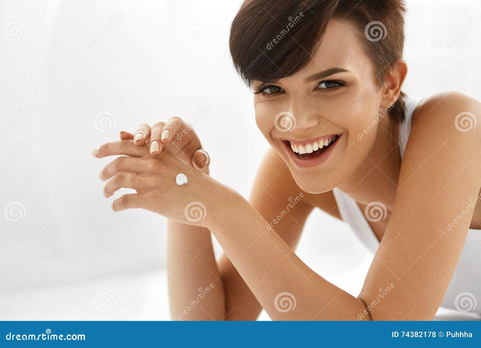 De zorg van de huid Mooie Gelukkige Vrouw met Handroom, Lotion op Hand