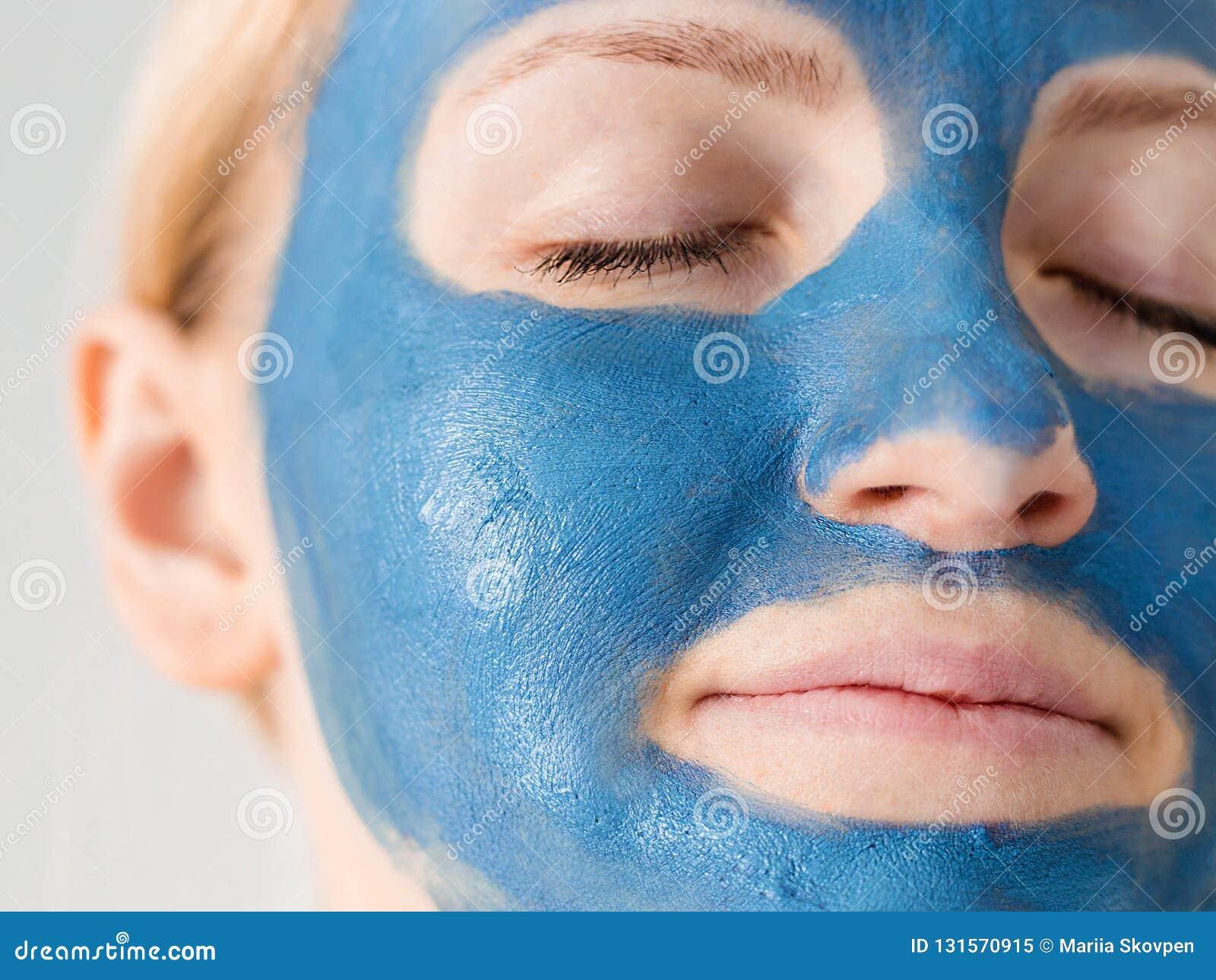 De zorg van de huid Vrouwengezicht met blauwe het masker dichte omhooggaand van de kleimodder Meisje die olieachtige teint behand