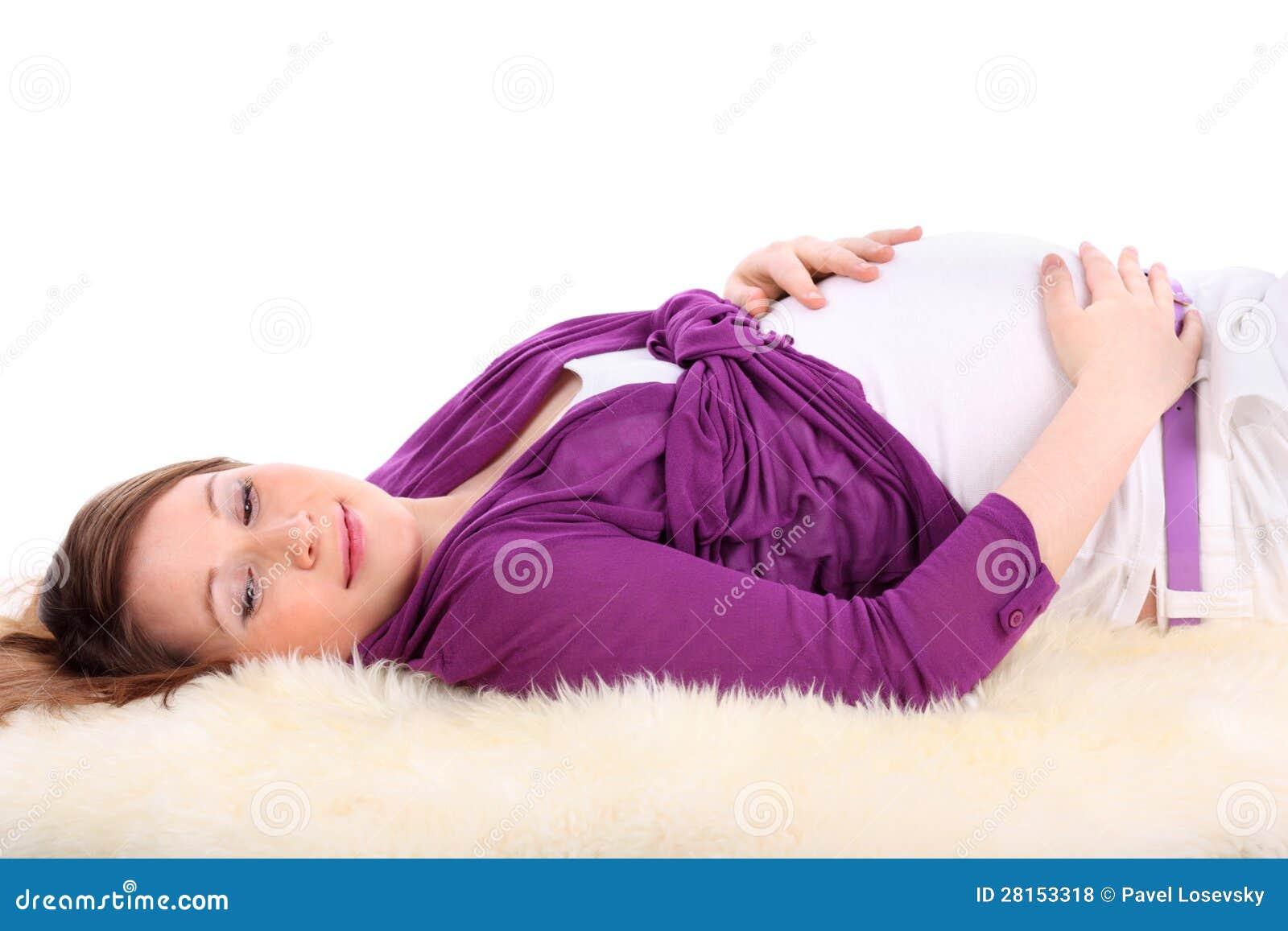 De zwangere vrouw ligt op bont en raakt buik