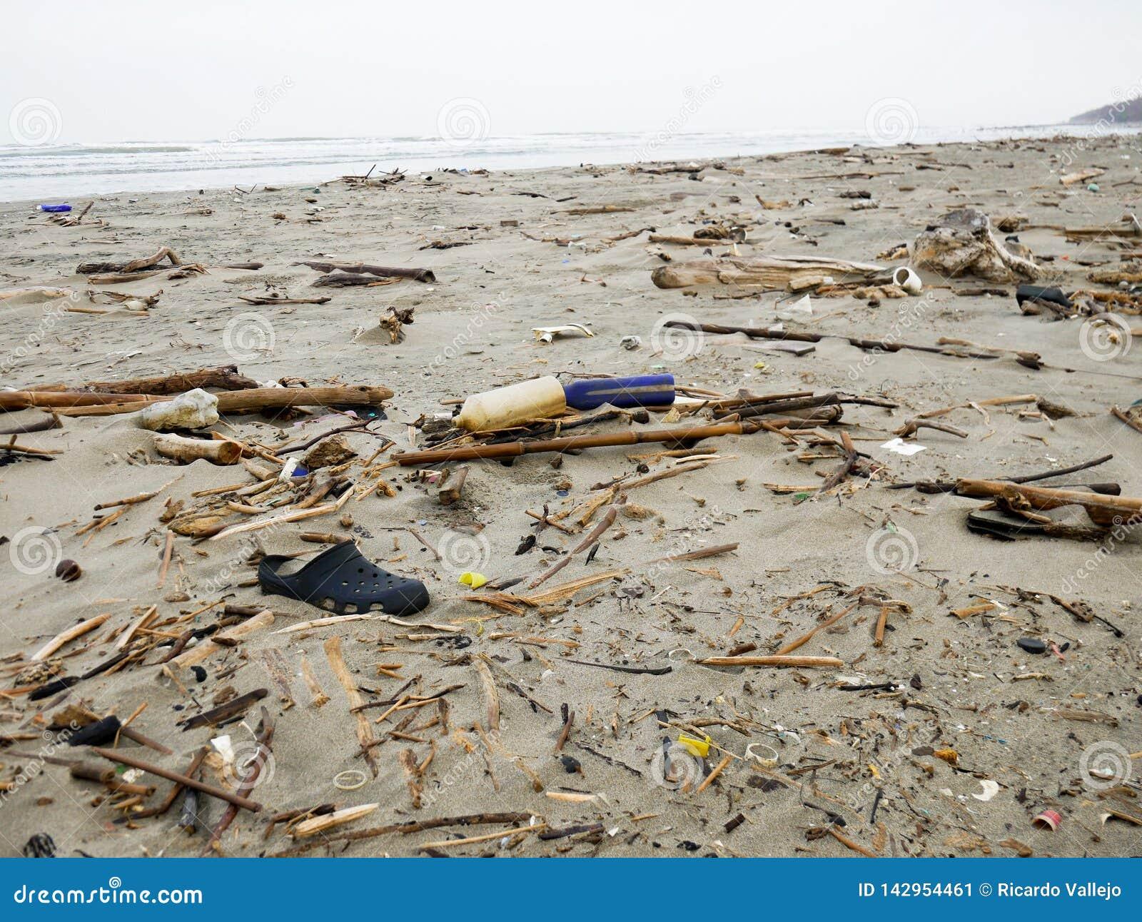 De zwarte belemmeringsschoen dumpte op een Caraïbisch strand dichtbij de plastic verontreiniging van Cartagena Colombia