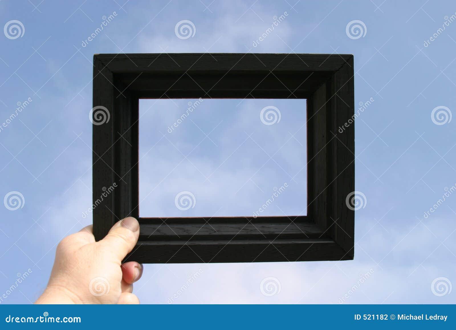 De zwarte omlijsting wordt gehouden tegen een blauwe hemel door een echte menselijke hand