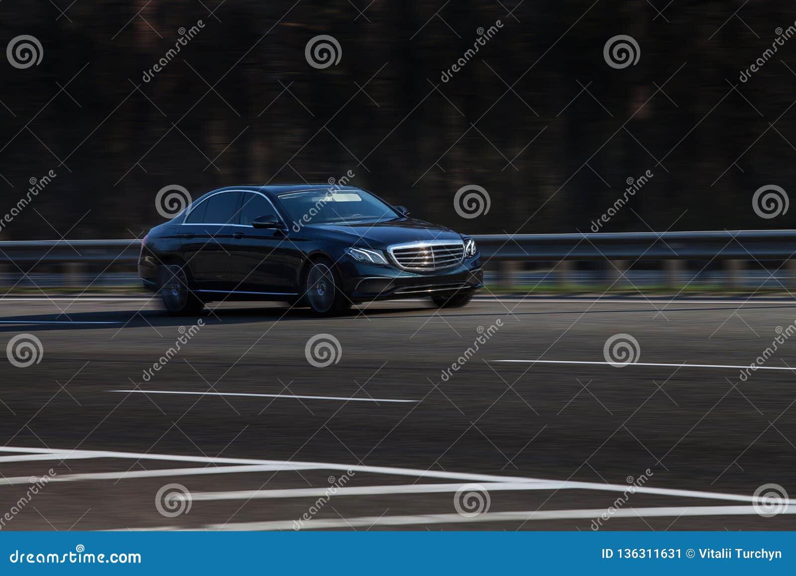 De zwarte ritten van Mercedes S op de weg Tegen een achtergrond van vage bomen