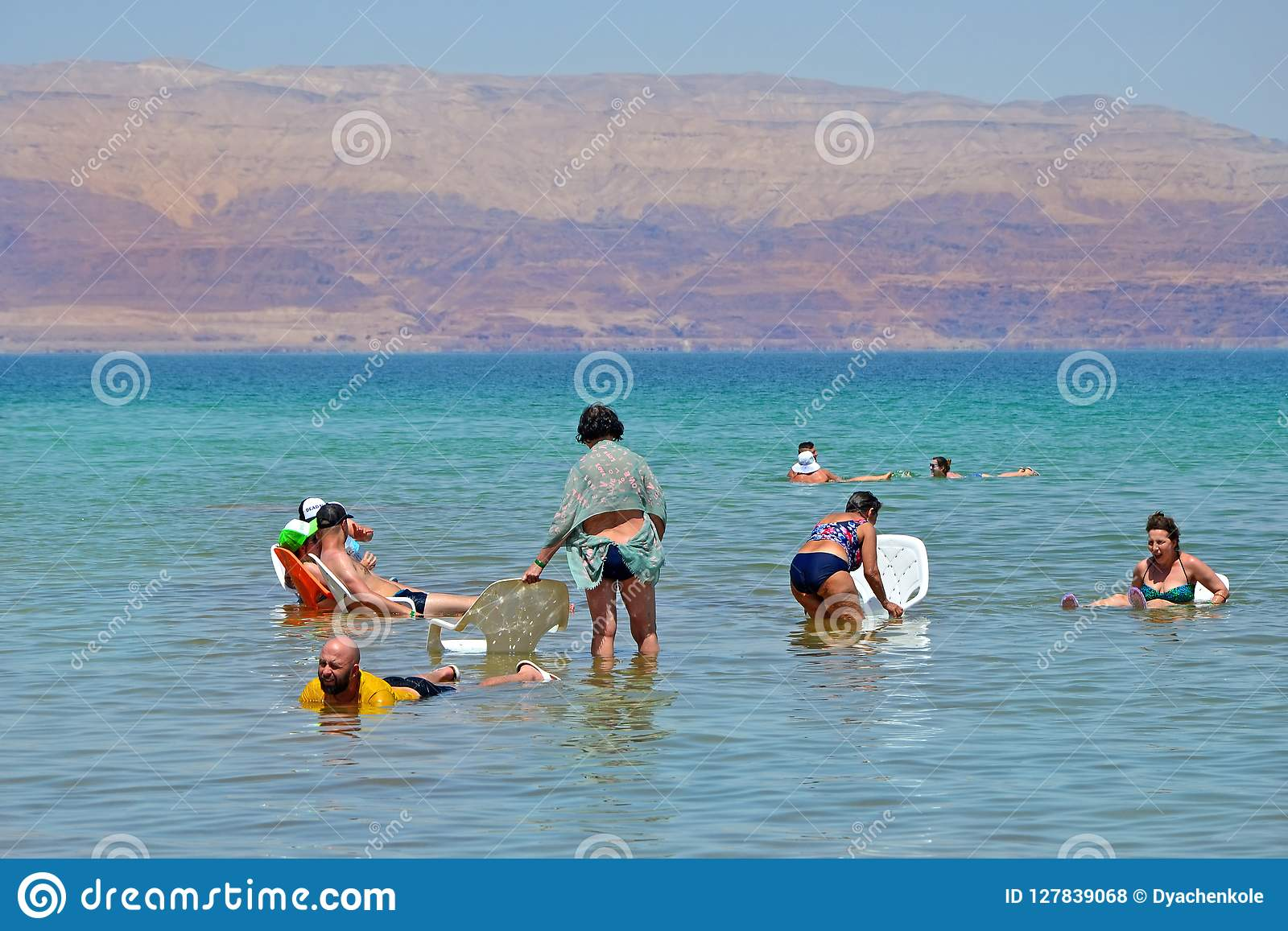 Dead sea, Israel - 31 MAY 2017: people on chairs relaxes and swims in the water of the Dead Sea in Israel. tourism,