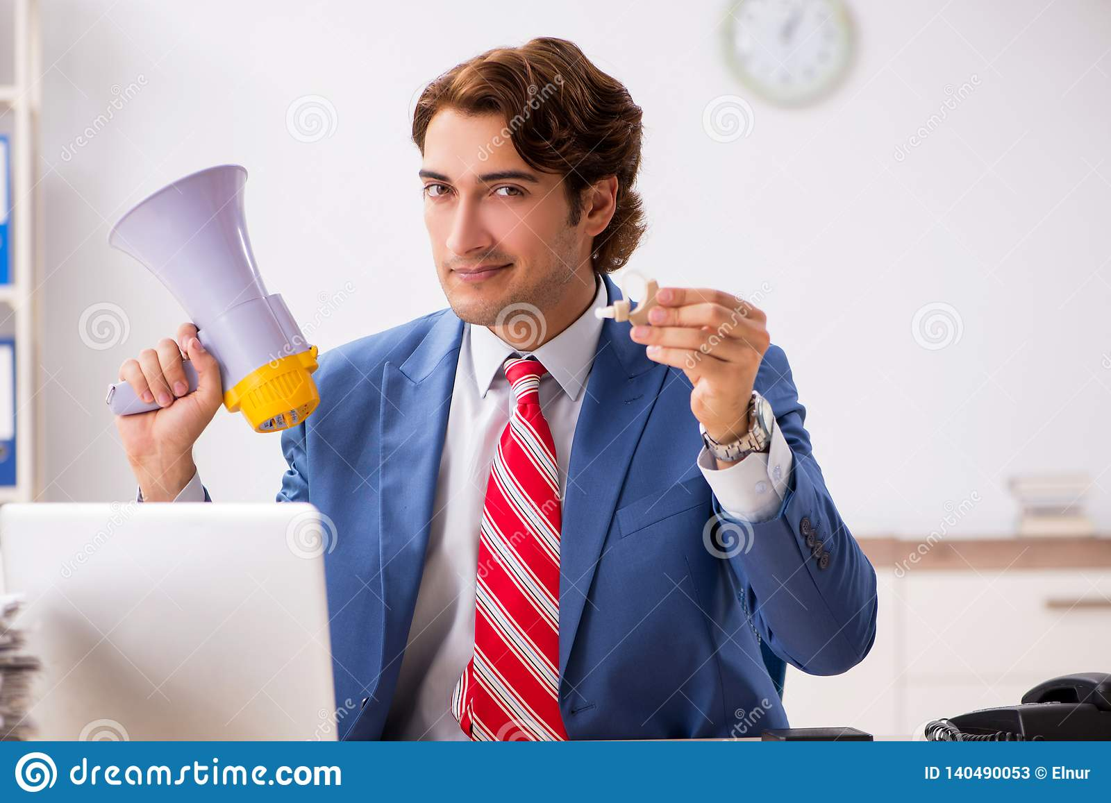 The deaf employee using hearing aid in office