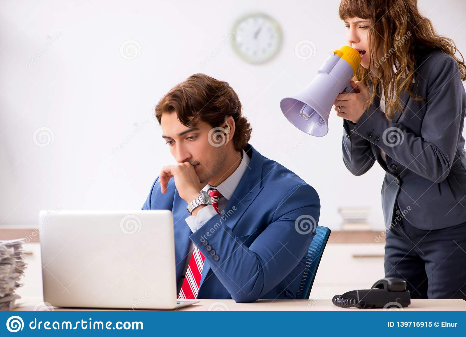 The deaf employee using hearing aid talking to boss